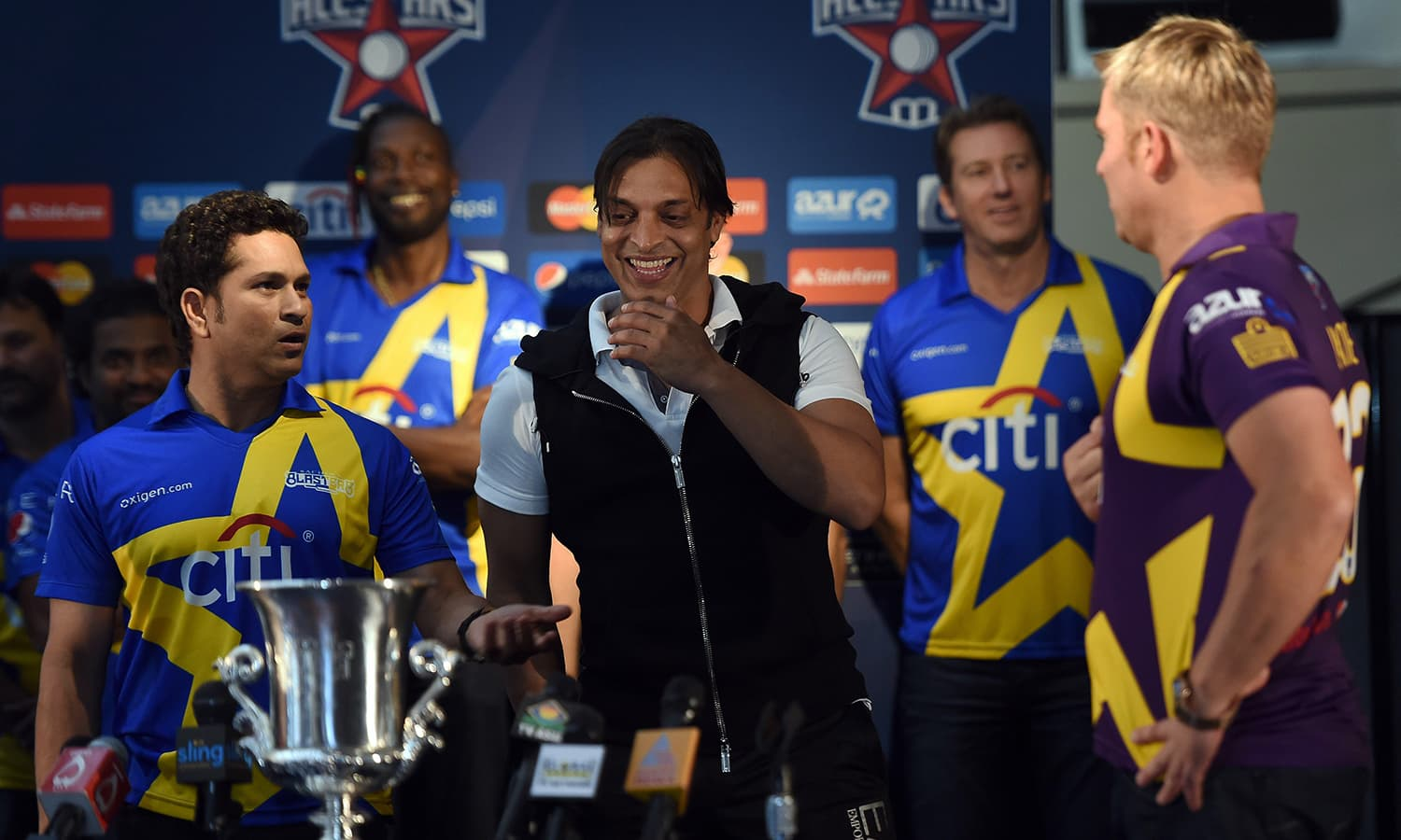"""Australia's Shane Warne (R) and Indian's Sachin Tendulkar (L) toss for Pakistan's Shoaib Akhtar during a press conference in New York on November 5, 2015. Tendulkar and Warne will lead a lineup of renowned cricket players from around the world in the inaugural """"Cricket All-Stars,"""" a three-game series to be played in Major League Baseball stadiums in New York , Houston and Los Angeles, to promote cricket the US. AFP PHOTO/JEWEL SAMAD"""