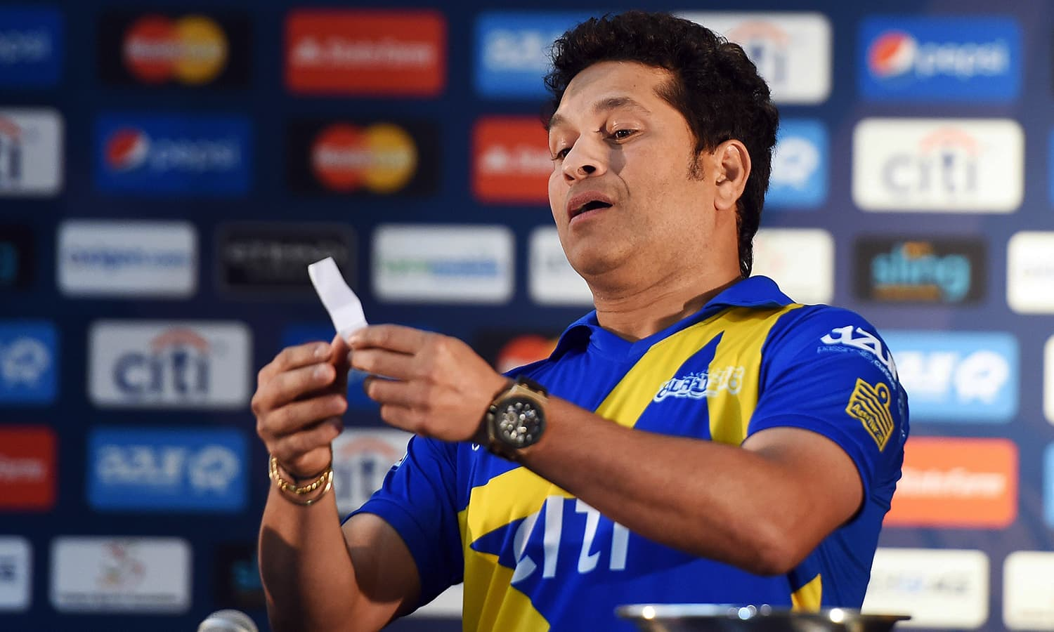 """Retired Indian cricketer Sachin Tendulkar reacts he draws the names of players during a press conference in New York on November 5, 2015. Tendulkar and Australia's Shane Warne will lead a lineup of renowned cricket players from around the world in the inaugural """"Cricket All-Stars,"""" a three-game series to be played in Major League Baseball stadiums in New York , Houston and Los Angeles, to promote cricket the US. AFP PHOTO/JEWEL SAMAD"""