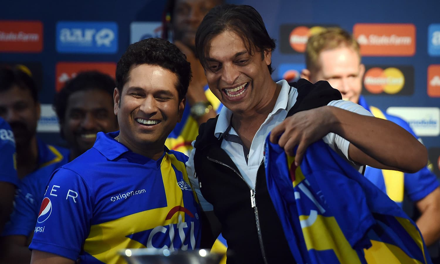 """Former Pakistan's fast bowler Shoaib Akhtar (R) hugs retired Indian cricketer Sachin Tendulkar after he was selected for Tendulkar's team during a press conference in New York on November 5, 2015. Tendulkar and Warne will lead a lineup of renowned cricket players from around the world in the inaugural """"Cricket All-Stars,"""" a three-game series to be played in Major League Baseball stadiums in New York , Houston and Los Angeles, to promote cricket the US. AFP PHOTO/JEWEL SAMAD"""