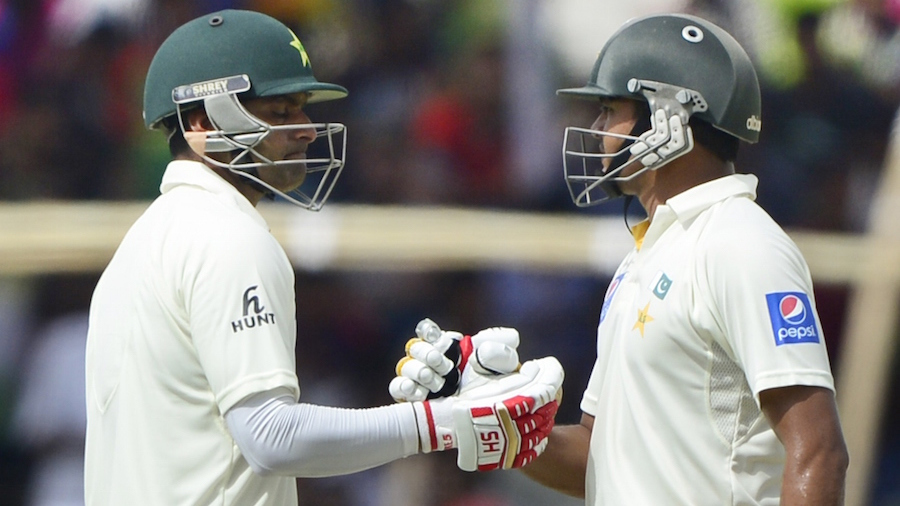 Pakistan cricketer Mohammad Hafeez (L) celebrates his half century (50 runs) with teammate Azhar Ali (R) during the second day of the first cricket Test match between Bangladesh and Pakistan at The Sheikh Abu Naser Stadium in Khulna on April 29, 2015. AFP PHOTO/Munir uz ZAMAN        (Photo credit should read MUNIR UZ ZAMAN/AFP/Getty Images)