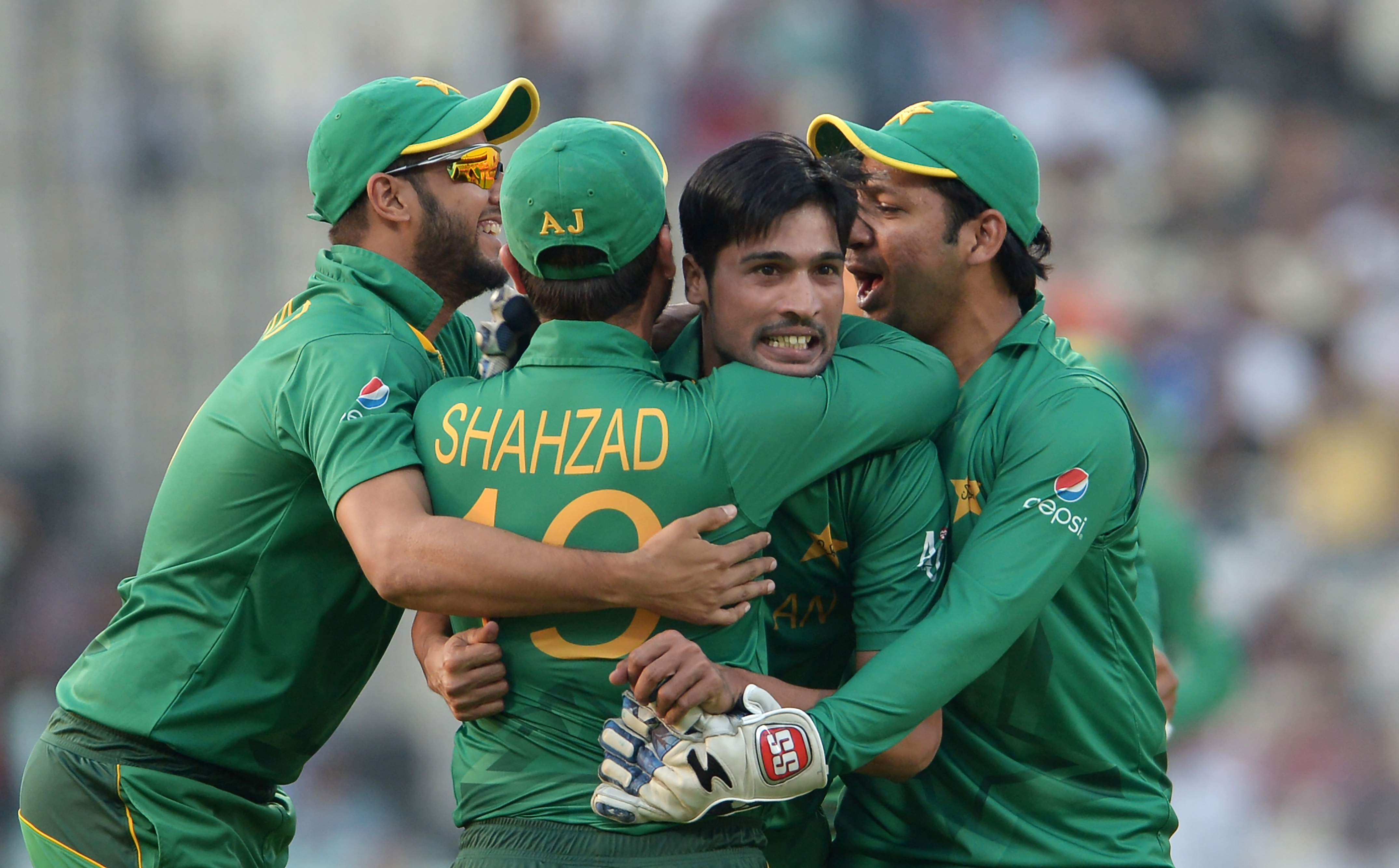 Pakistan's Mohammad Amir(2R)celebrates with teammates after the dismissal of Bangladesh's Soumya Sarkar during the World T20 cricket tournament match between Pakistan and Bangladesh at The Eden Gardens Cricket Stadium in Kolkata on March 16, 2016.  / AFP / Dibyangshu SARKAR