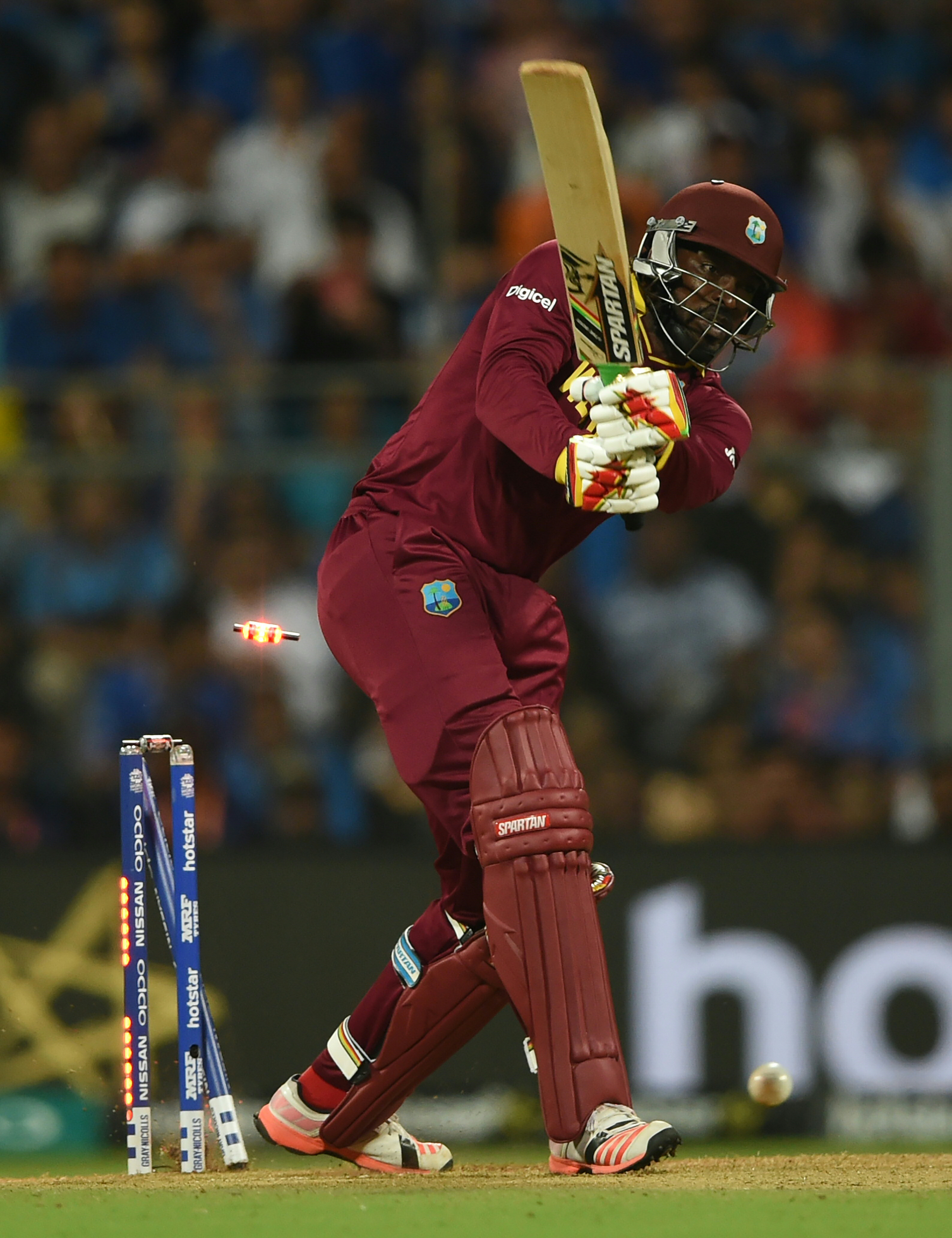 West Indies's Chris Gayle is bowled out during the World T20 men's semi-final match between India and West Indies at The Wankhede Cricket Stadium in Mumbai on March 31, 2016. / AFP / INDRANIL MUKHERJEE