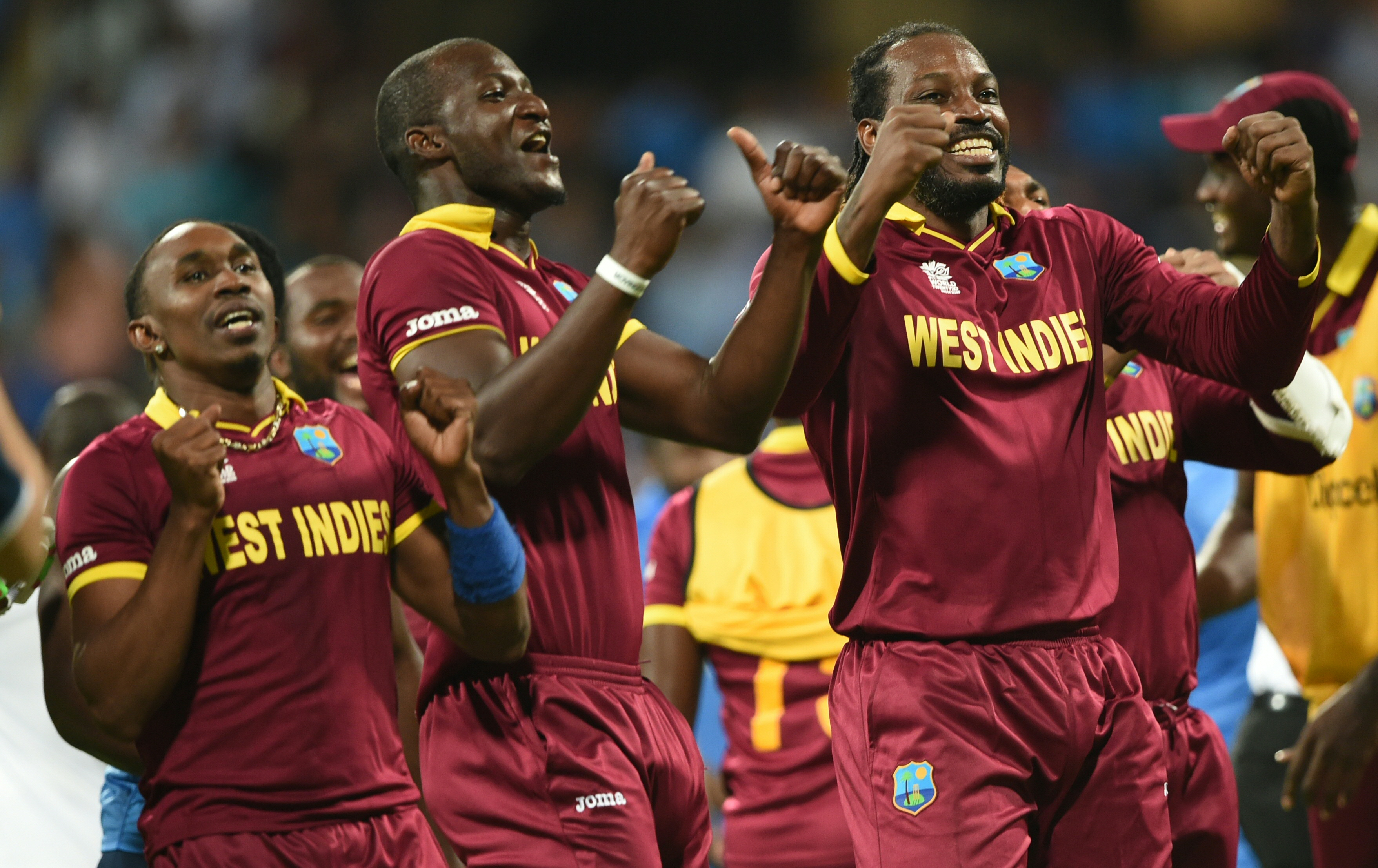 West Indies's captain Darren Sammy(C) Dwayne Bravo(L)and Chris Gayle(R)celebrate after victory in the World T20 cricket tournament second semi-final match between India and West Indies at The Wankhede Stadium in Mumbai on March 31, 2016. / AFP / INDRANIL MUKHERJEE