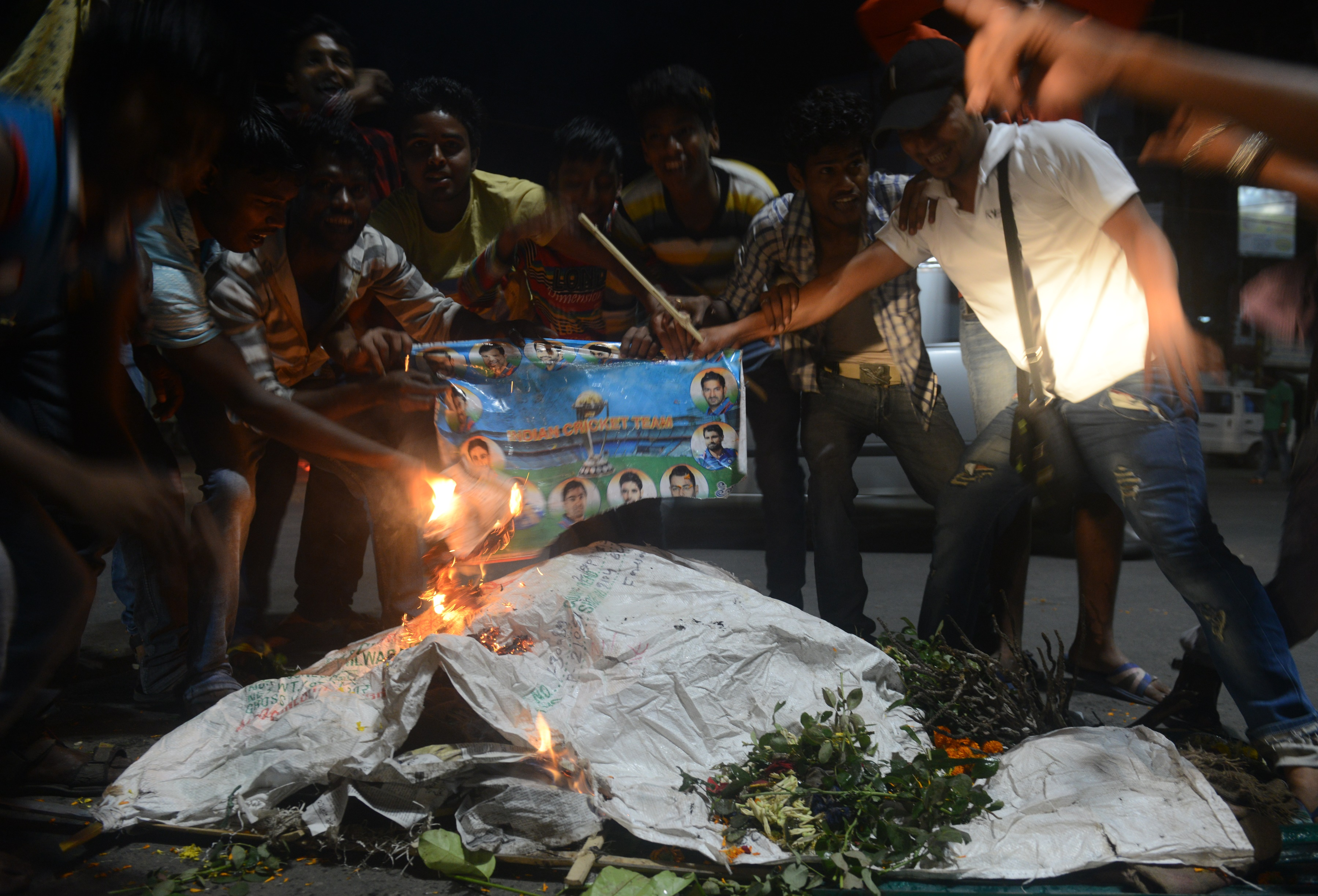 "Indian cricket fans burn portraits of players as they stage a funeral of the Indian cricket team in the streets of Siliguri on March 31, 2016, after India's defeat in the men's semi-final match between India and West Indies in a World T20 cricket tournament match played at Mumbai. The West Indies achieved their ""mission"" of shattering India's dreams of a World Twenty20 title on home soil after they stunned the hosts by seven wickets to reach the final on March 31, 2016. / AFP / DIPTENDU DUTTA"