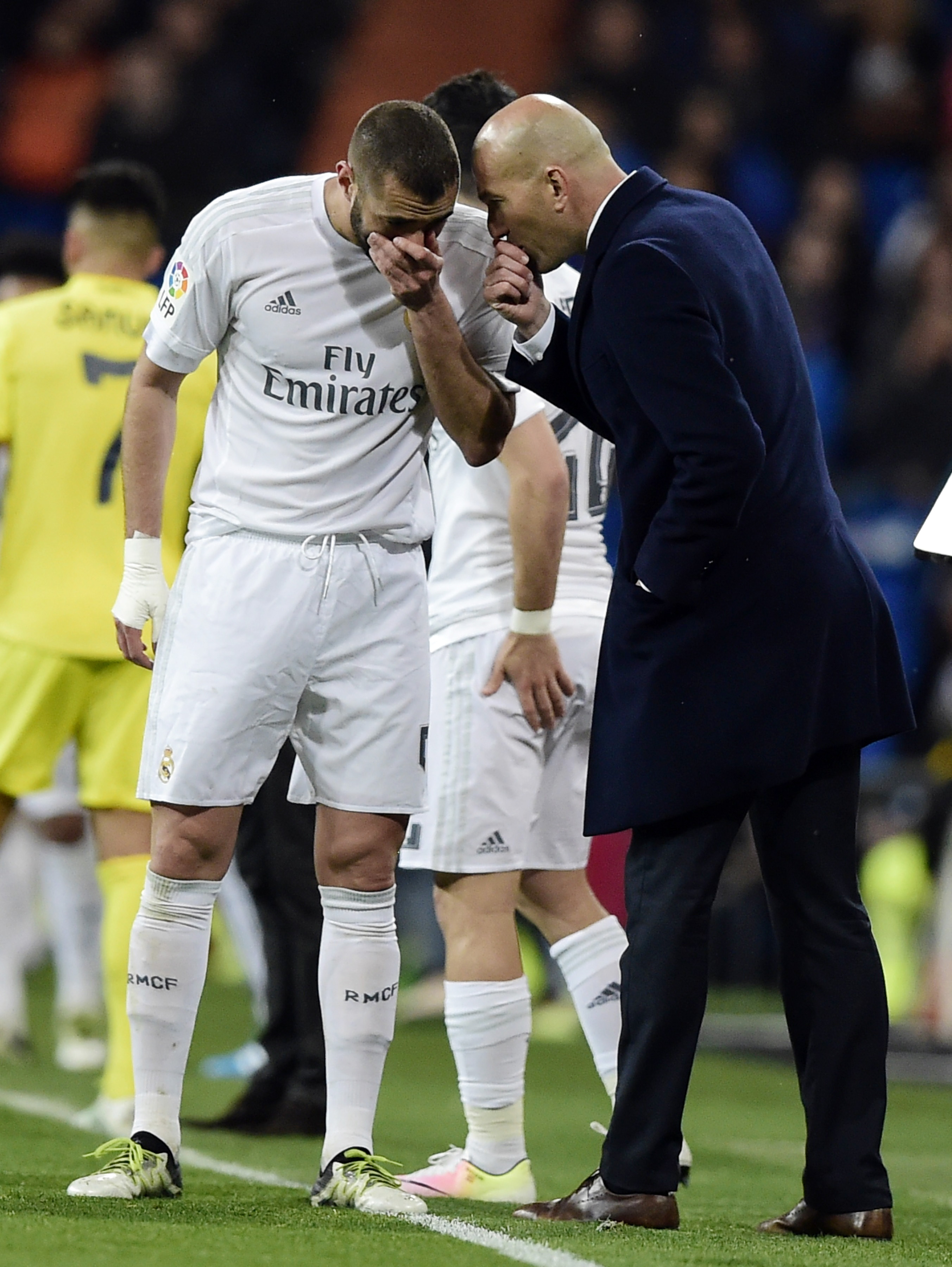 Real Madrid's French forward Karim Benzema (L) speaks with Real Madrid's French coach Zinedine Zidane during the Spanish league football match Real Madrid CF vs Villarreal CF at the Santiago Bernabeu stadium in Madrid on April 20, 2016. / AFP PHOTO / JAVIER SORIANO