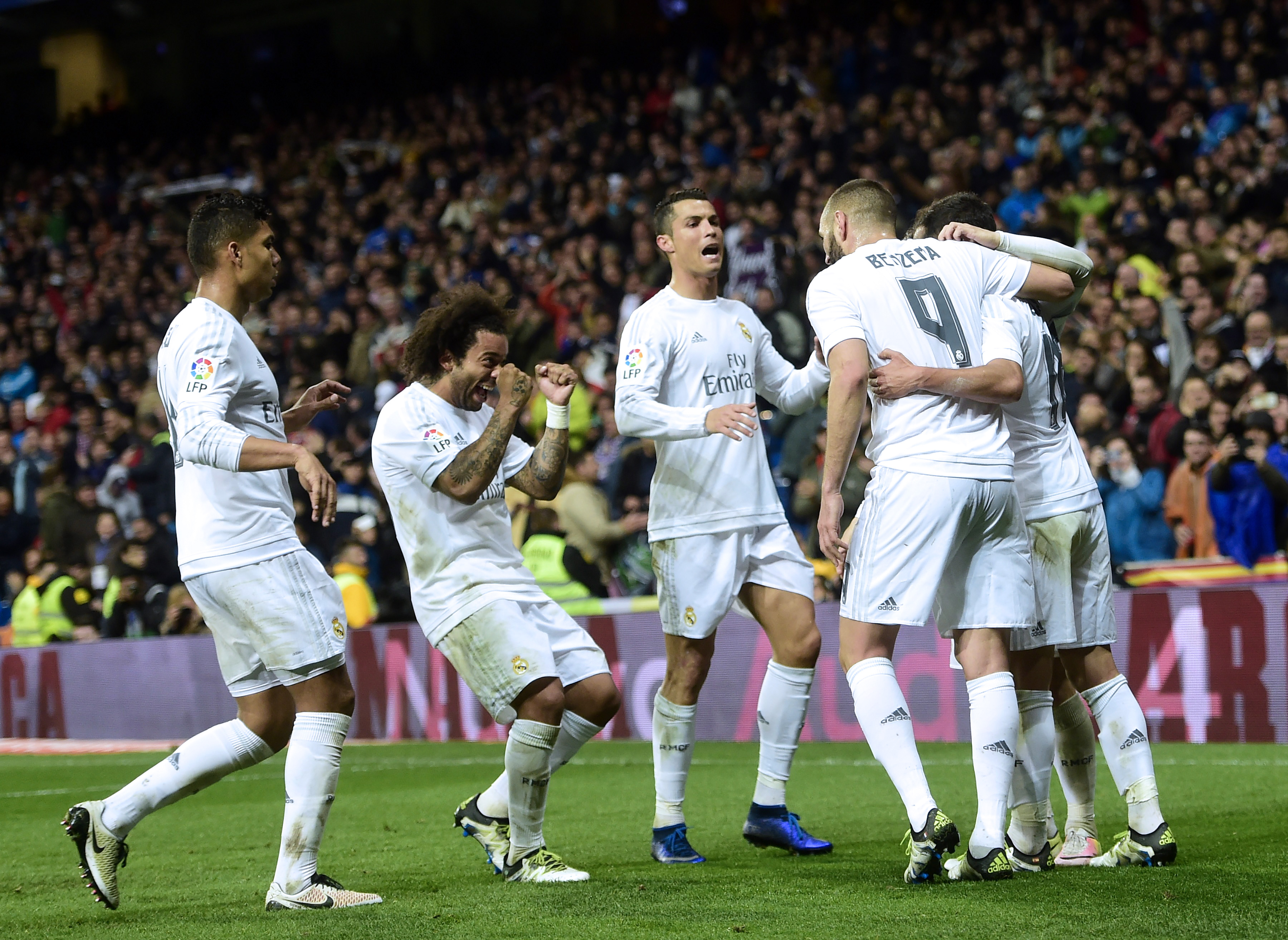 Real Madrid's players celebrate a goal during the Spanish league football match Real Madrid vs Villarreal at the Santiago Bernabeu stadium in Madrid on April 20, 2016. / AFP PHOTO / PIERRE-PHILIPPE MARCOU