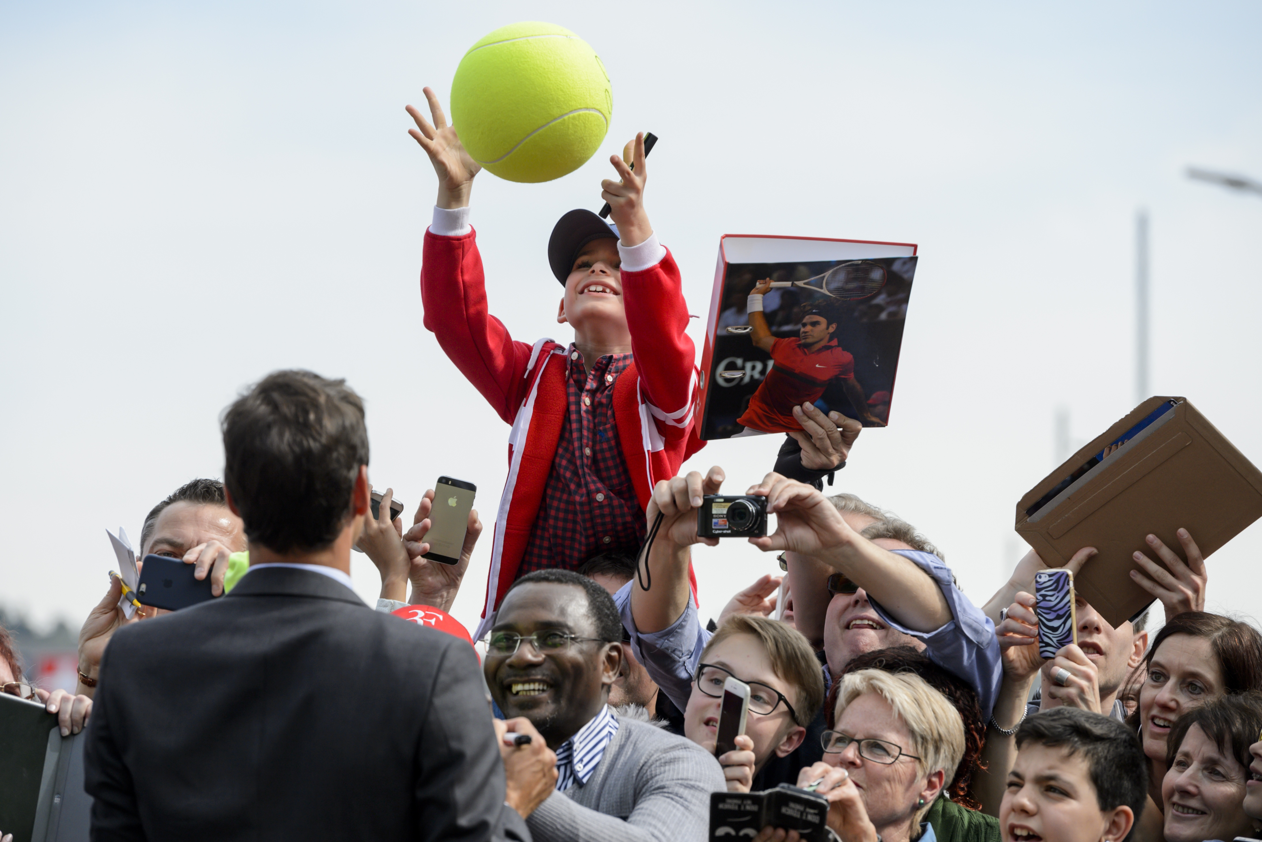 A young fan receives back his giant ball signed by Swiss tennis champion Roger Federer (back) during a ceremony to unveil a street bearing his name on April 21, 2016 in Biel, western Switzerland. The street located next to the Swiss tennis center where Federer completed its tennis studies. / AFP PHOTO / FABRICE COFFRINI