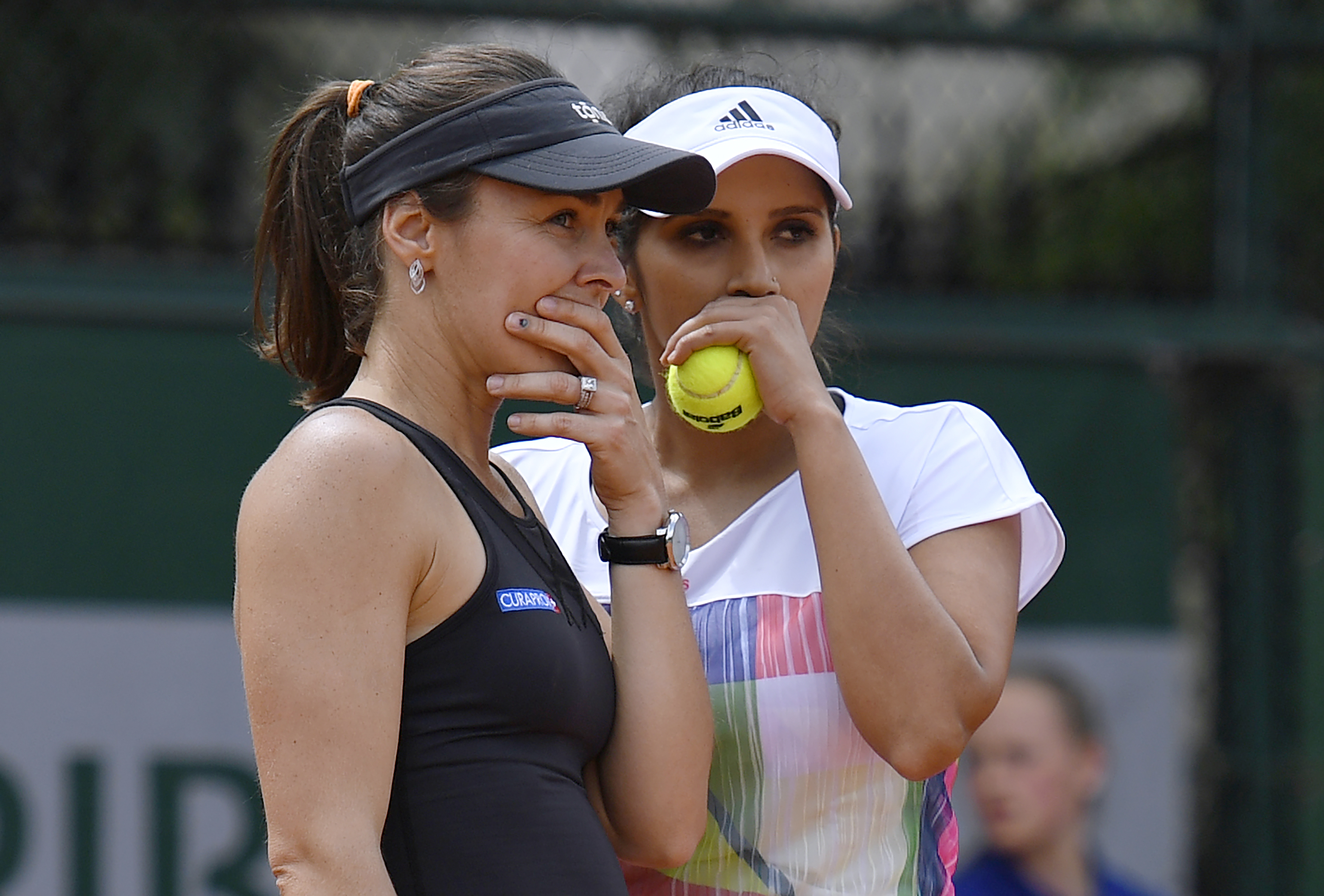 Switzerland's Martina Hingis (L) speaks to her teammate India's Sania Mirza during their women's first round doubles match against Russia's Daria Kasatkina and Alexandra Panova at the Roland Garros 2016 French Tennis Open in Paris on May 25, 2016. / AFP PHOTO / MARTIN BUREAU