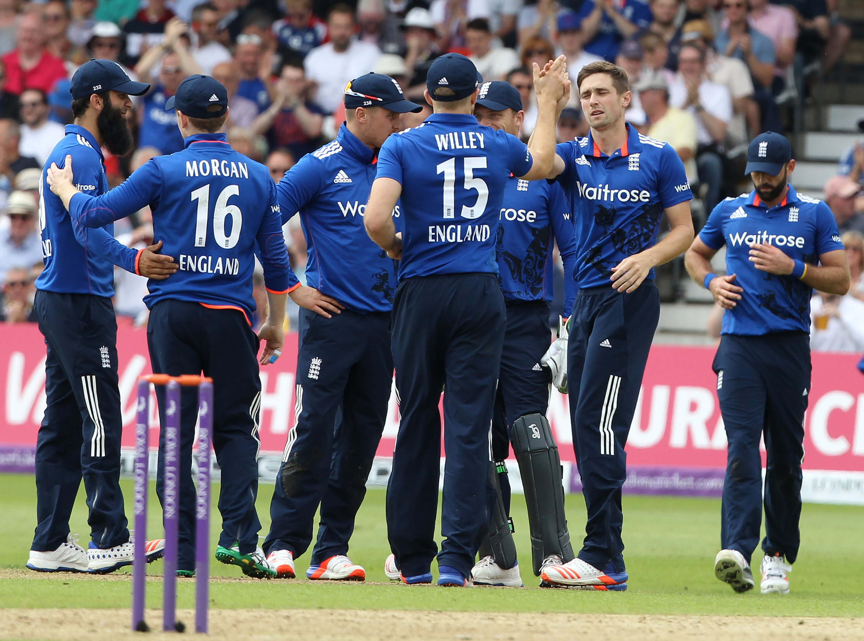 England's Chris Woakes (2nd R) celebrates with teammates after taking the wicket of Sri Lanka's Seekkuge Prasanna (not pictured) during play in the first one day international (ODI) cricket match between England and Sri Lanka at Trent Bridge cricket ground in Nottingham, central England, on June 21, 2016. England captain Eoin Morgan won the toss and elected to field against Sri Lanka in the first one-day international at Trent Bridge on Tuesday. / AFP PHOTO / Lindsey PARNABY