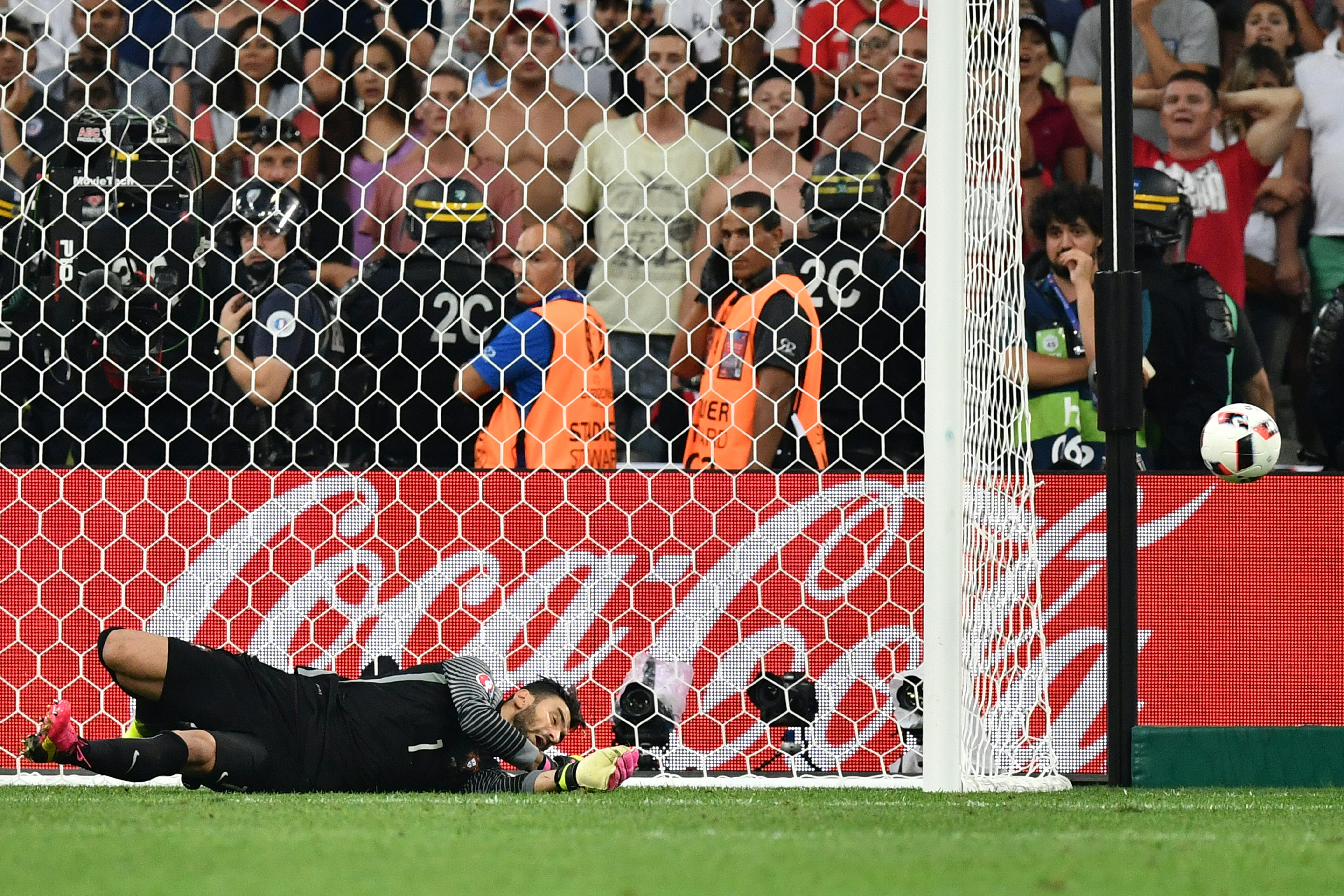 Portugal's goalkeeper Rui Patricio stops a shot in a penalty shoot-out during the Euro 2016 quarter-final football match between Poland and Portugal at the Stade Velodrome in Marseille on June 30, 2016. / AFP PHOTO / BERTRAND LANGLOIS