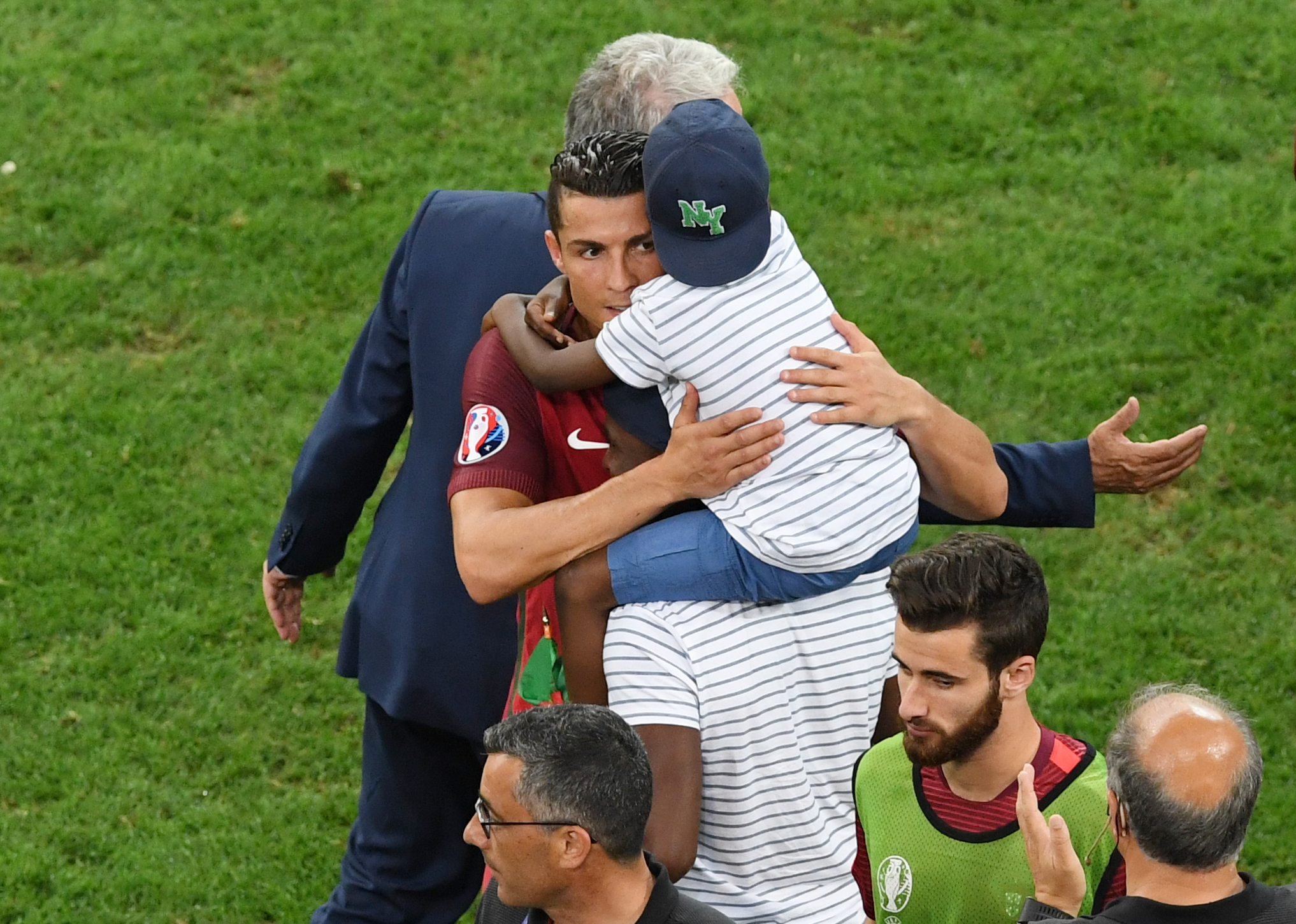 Portugal's forward Cristiano Ronaldo hugs a child after the Euro 2016 quarter-final football match between Poland and Portugal at the Stade Velodrome in Marseille on June 30, 2016. / AFP PHOTO / BORIS HORVAT