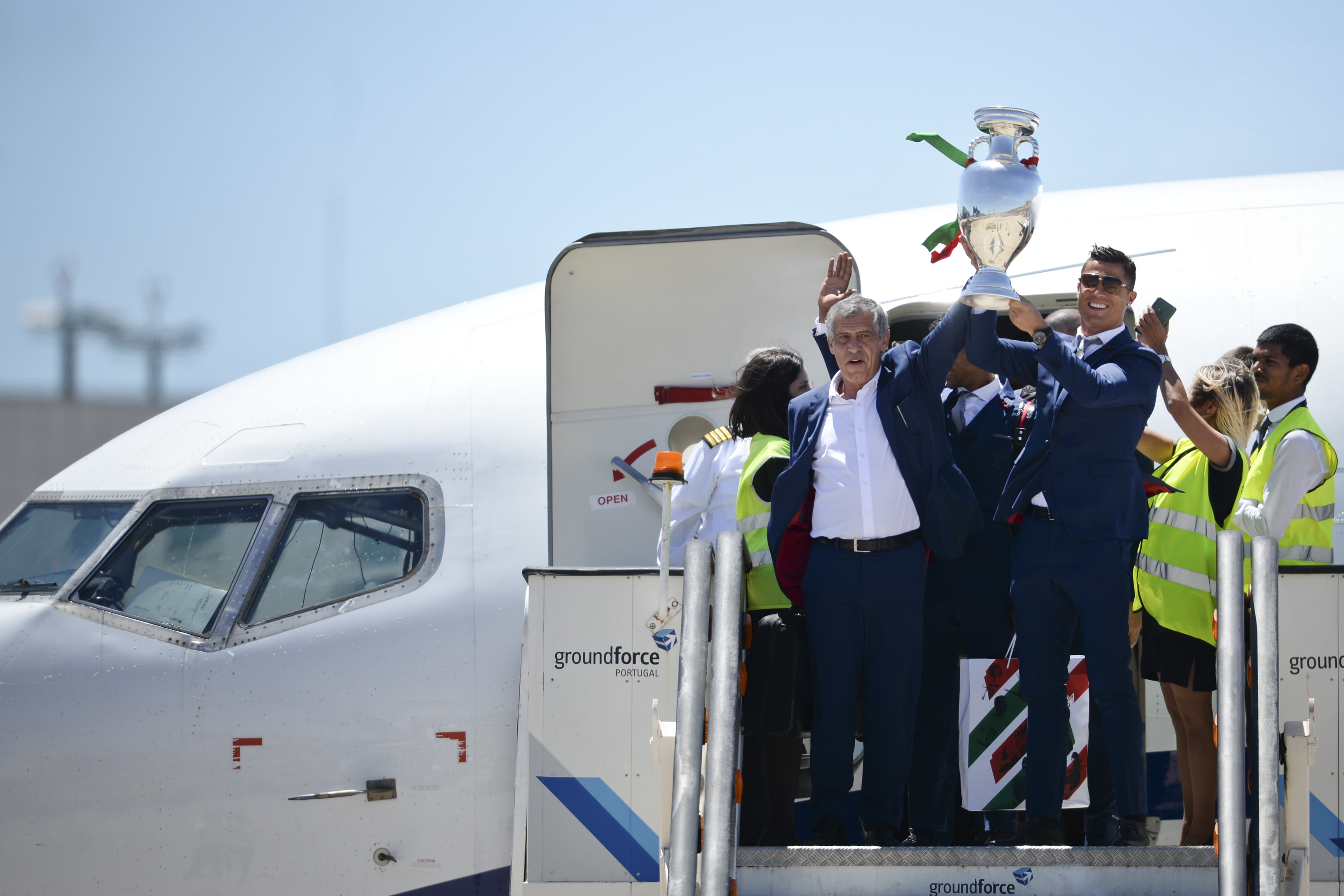 Portugal's head coach Fernando Santos (L) and Portugal's forward Cristiano Ronaldo (R) hold the trophy on arrival at Lisbon airport on July 11, 2016 after their Euro 2016 final football win over France yesterday. The Portuguese football team led by Cristiano Ronaldo returned home to a heroes' welcome today after their upset 1-0 win triumph over France in the Euro 2016 final.  / AFP PHOTO / PATRICIA DE MELO MOREIRA