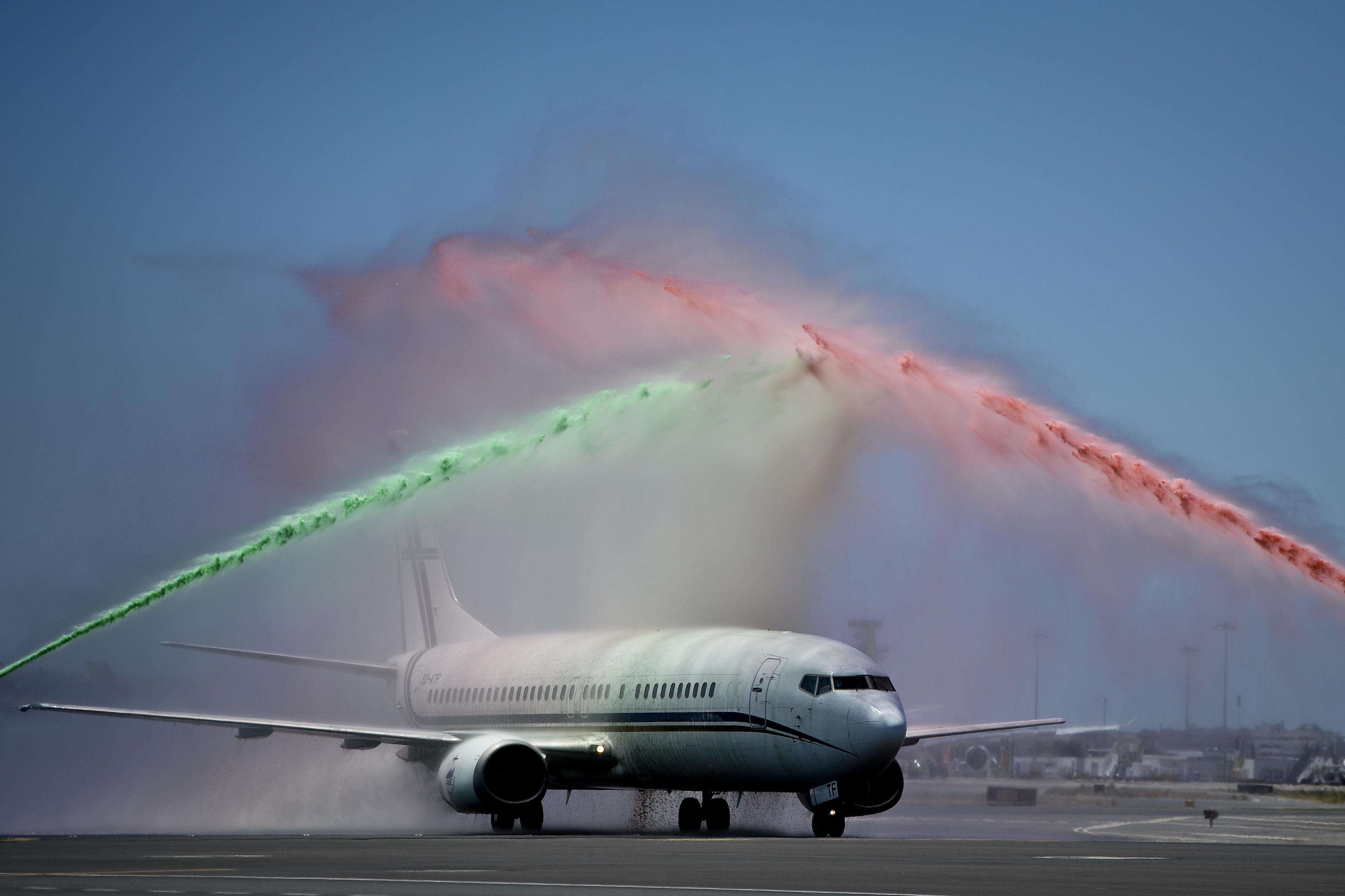 An airport firefighter's unit spray water in the national colours over the aircraft carrying Portugal's national football team members during a welome at Lisbon airport on July 11, 2016 after the Euro 2016 final football win over France yesterday. The Portuguese football team led by Cristiano Ronaldo returned home to a heroes' welcome today after their upset 1-0 win triumph over France in the Euro 2016 final.  / AFP PHOTO / PATRICIA DE MELO MOREIRA