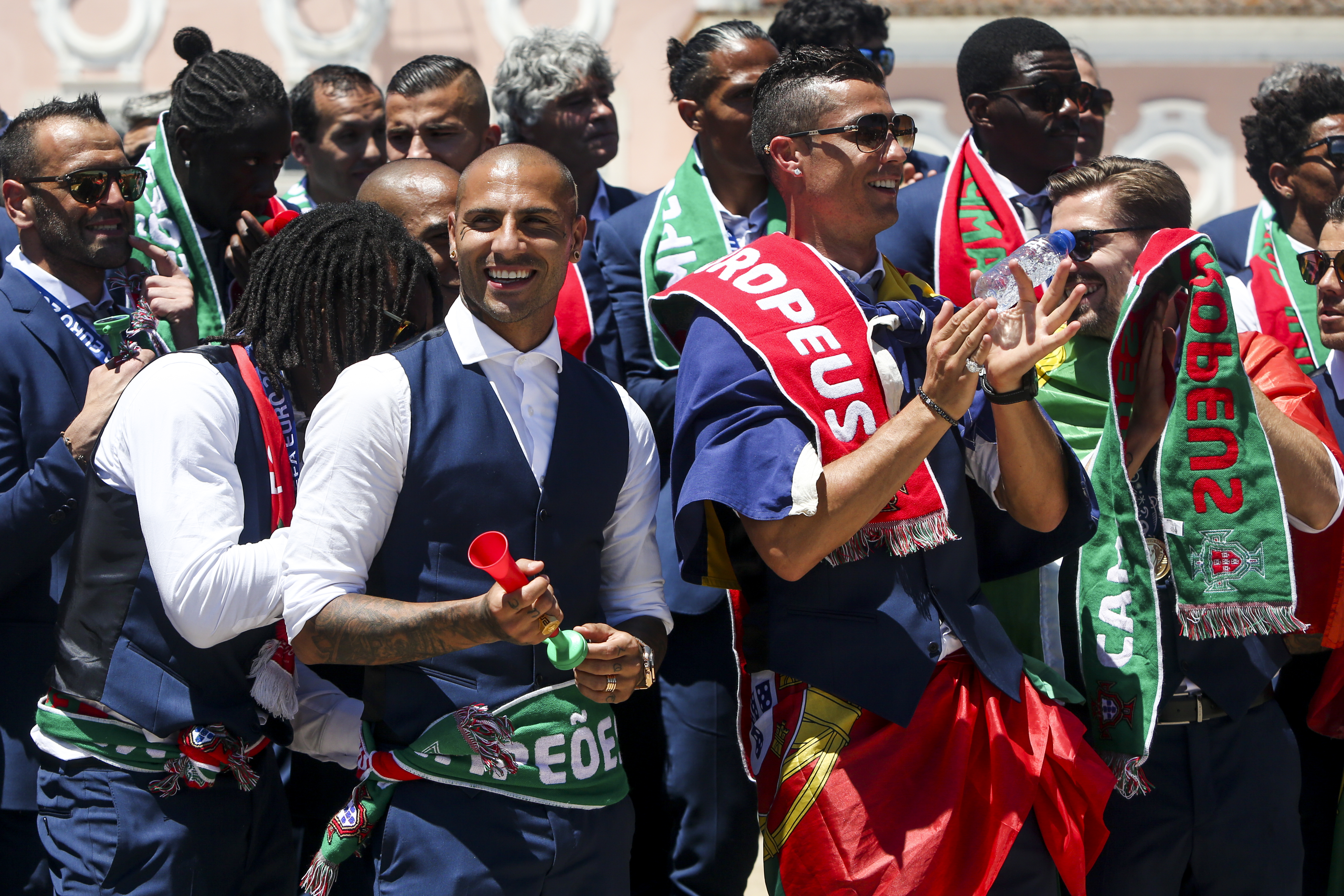 Portugal's forward Cristiano Ronaldo (R) applauds Portugal's President Marcelo Rebelo de Sousa (unseen) past Portugal's forward Ricardo Quaresma (L) as they celebrate their victory at Belem Palace on July 11, 2016 after their Euro 2016 final football win over France yesterday. The Portuguese football team led by Cristiano Ronaldo returned home to a heroes' welcome today after their upset 1-0 win triumph over France in the Euro 2016 final.  / AFP PHOTO / NUNO FOX