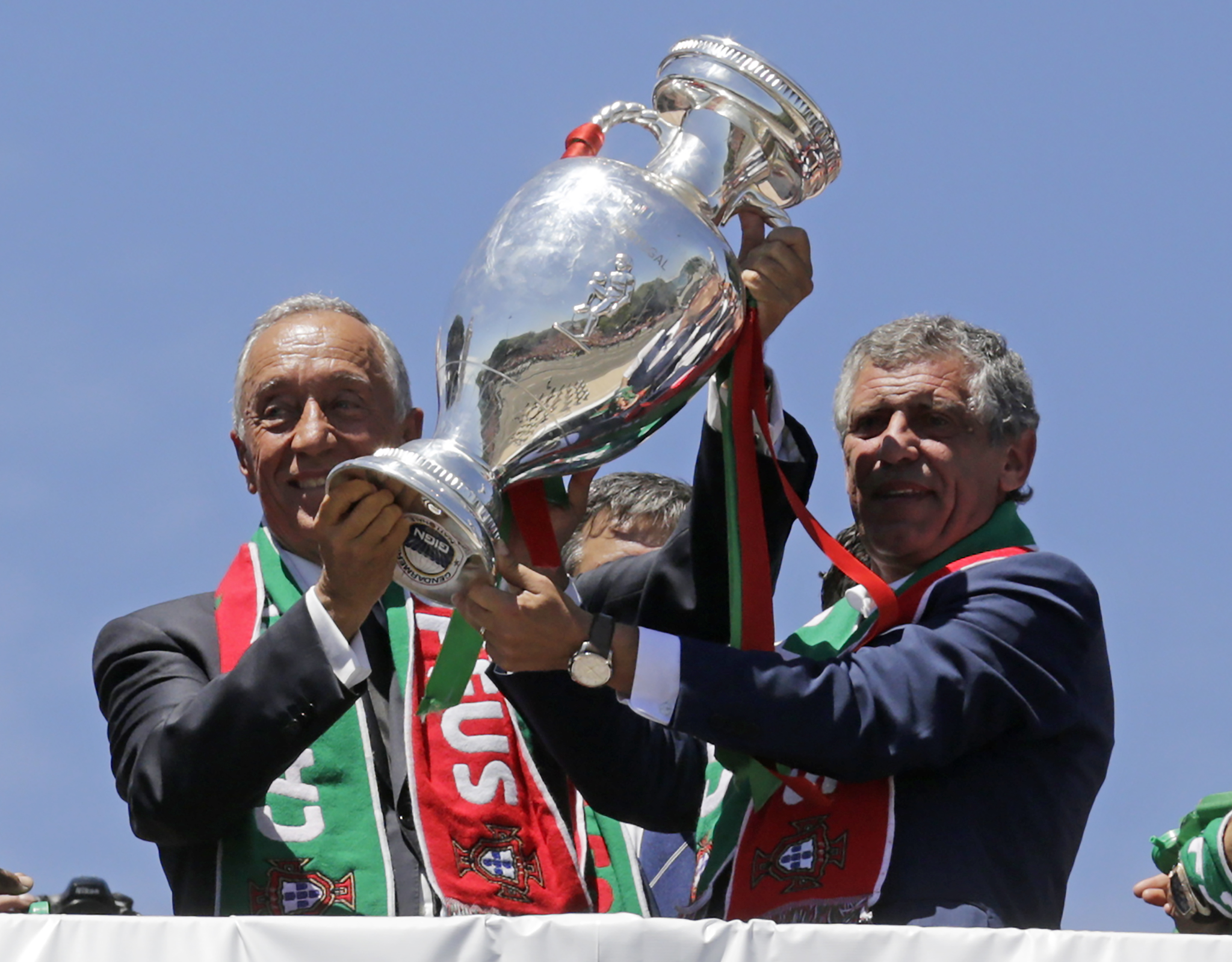 Portugal's president Marcelo Rebelo de Sousa (L) and Portugal's coach Fernando Santos hold the trophy on the balcony of the Belem Palace as they celebrate their victory on July 11, 2016 after their Euro 2016 final football win over France yesterday. The Portuguese football team led by Cristiano Ronaldo returned home to a heroes' welcome today after their upset 1-0 win triumph over France in the Euro 2016 final.  / AFP PHOTO / JOSE MANUEL RIBEIRO