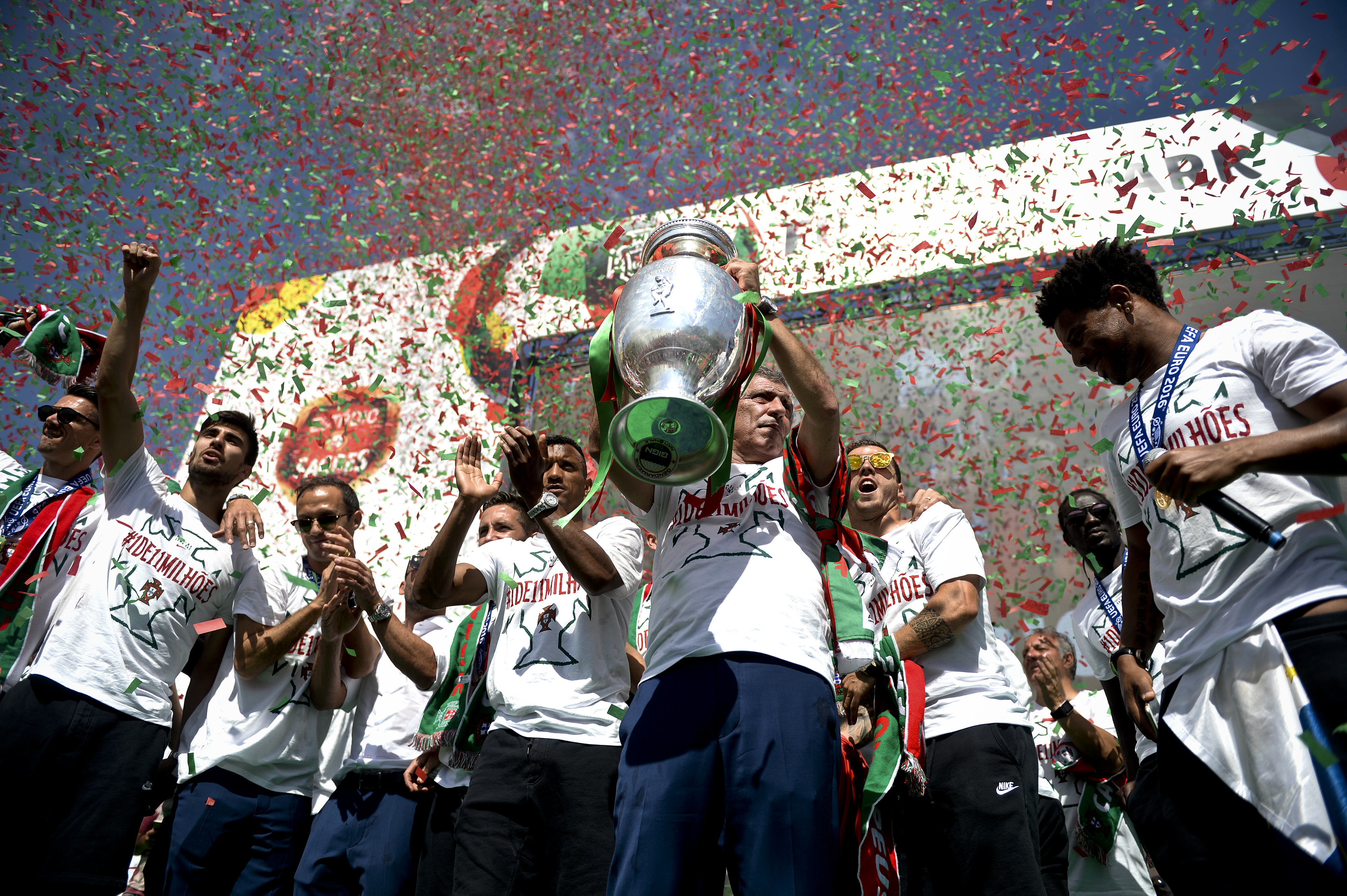 Portugal's head coach Fernando Santos (C) holds the trophy as he celebrates with his players on a stage at Alameda square in Lisbon on July 11, 2016 where thousands of supporters welcome them with scarfs and flags to celebrate their victory over France in their Euro 2016 final played yesterday. The Portuguese football team returned home to a heroes' welcome today after their upset 1-0 win triumph over France in the Euro 2016 final.  / AFP PHOTO / PATRICIA DE MELO MOREIRA