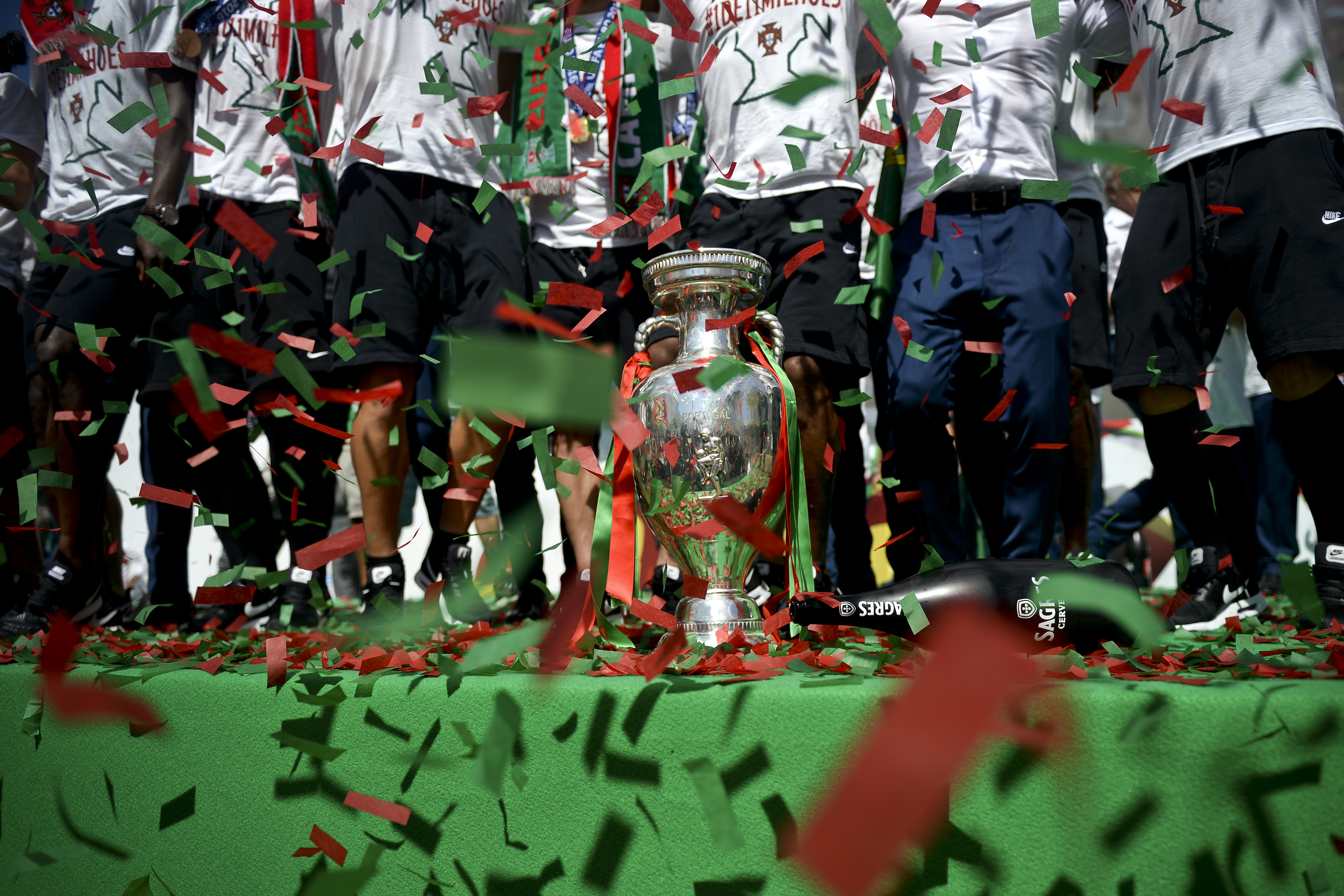 Portugal's football team players jump and sing next tto the trophy displayed on a stage at Alameda square in Lisbon on July 11, 2016 where thousands of supporters welcome them with scarfs and flags to celebrate their victory over France in their Euro 2016 final played yesterday. The Portuguese football team returned home to a heroes' welcome today after their upset 1-0 win triumph over France in the Euro 2016 final.  / AFP PHOTO / PATRICIA DE MELO MOREIRA
