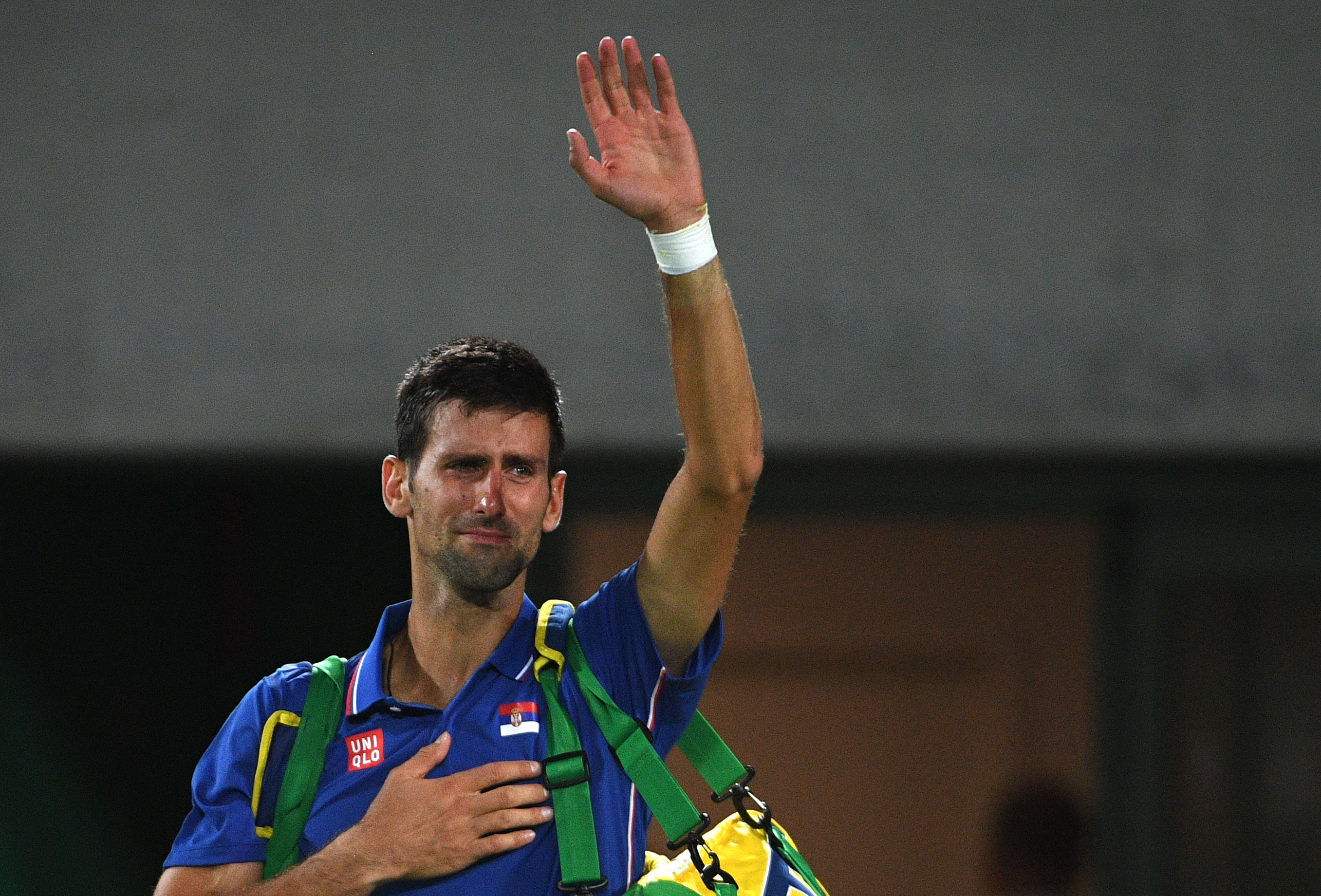 Serbia's Novak Djokovic waves to the crowd with tears in his eyes after losing his men's first round singles tennis match against Argentina's Juan Martin Del Potro at the Olympic Tennis Centre of the Rio 2016 Olympic Games in Rio de Janeiro on August 7, 2016. / AFP PHOTO / Roberto SCHMIDT