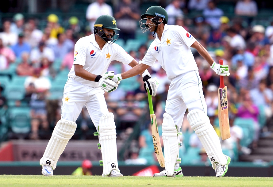 Pakistan batsmen Azhar Ali (L) and Younis Khan (R) shake hands during their partnership against Australia during the second day of the third cricket Test match at the SCG in Sydney on January 4, 2017. / AFP PHOTO / WILLIAM WEST / IMAGE RESTRICTED TO EDITORIAL USE - STRICTLY NO COMMERCIAL USE