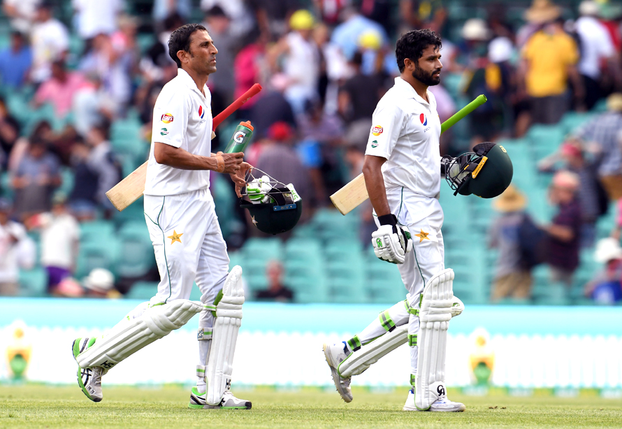 Pakistan batsmen Younis Khan (L) and Azhar Ali (R) walk off the stumps after defying Australia on the second day of the third cricket Test match at the SCG in Sydney on January 4, 2017. / AFP PHOTO / WILLIAM WEST / IMAGE RESTRICTED TO EDITORIAL USE - STRICTLY NO COMMERCIAL USE