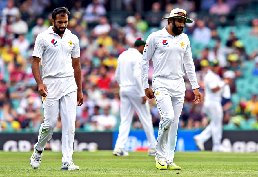 Pakistan paceman Wahab Riaz (L) and captain Misbah-ul-Haq (R) walk back to their mark as Australia's batsmen punish the bowling during the first day of the third cricket Test match at the SCG in Sydney on January 3, 2017. / AFP PHOTO / WILLIAM WEST / IMAGE RESTRICTED TO EDITORIAL USE - STRICTLY NO COMMERCIAL USE