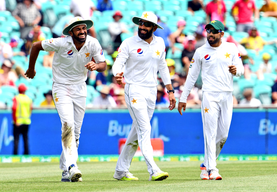 Pakistan fieldsman Wahab Riaz (L) hobbles off in pain as Misbah-ul-Haq (C) and Mohammad Rizwan (R) look on as Australia declares their innings closed during the second day of the third cricket Test match at the SCG in Sydney on January 4, 2017. / AFP PHOTO / WILLIAM WEST / --IMAGE RESTRICTED TO EDITORIAL USE - STRICTLY NO COMMERCIAL USE--
