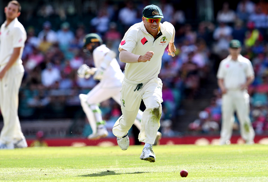 Australia's David Warner (C) chases the ball as the Pakistan batsmen take more runs during the second day of the third cricket Test match at the SCG in Sydney on January 4, 2017. / AFP PHOTO / WILLIAM WEST / IMAGE RESTRICTED TO EDITORIAL USE - STRICTLY NO COMMERCIAL USE