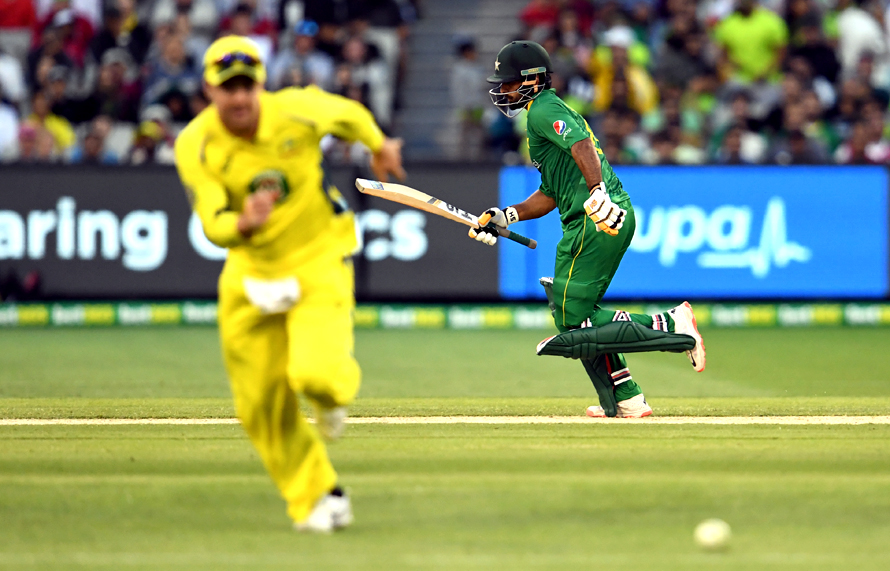 Pakistan batsman Mohammad Hafeez takes more runs from Australia's bowling as Travis Head chases the ball. (PHOTO: AFP)