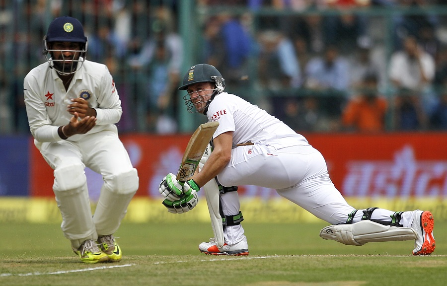 India's Cheteshwar Pujara, left, reacts after South Africa's AB de Villiers played a shot during the first day of their second cricket test match in Bangalore, India, Saturday, Nov. 14, 2015. (AP Photo/Aijaz Rahi)