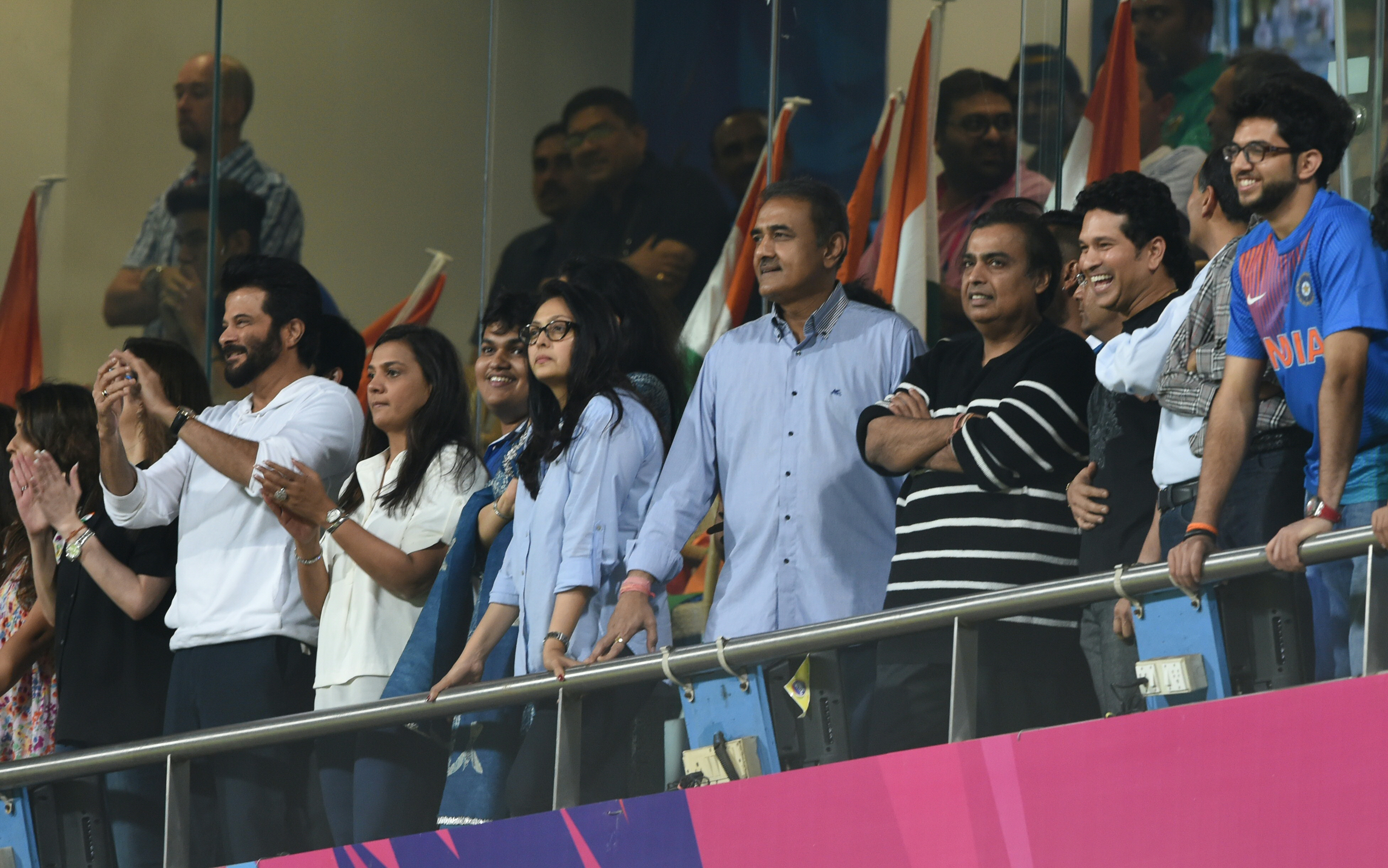 Indian Bollywood actor Anil Kapoor(L)industrialist Mukesh Ambani(3R),Sachin Tendulkar politician Praful Patil(4L)and Nita Ambani(3L)applaud after India's Virat Kohli scored his half century during the World T20 men's semi-final match between India and West Indies at The Wankhede Cricket Stadium in Mumbai on March 31, 2016. / AFP / INDRANIL MUKHERJEE