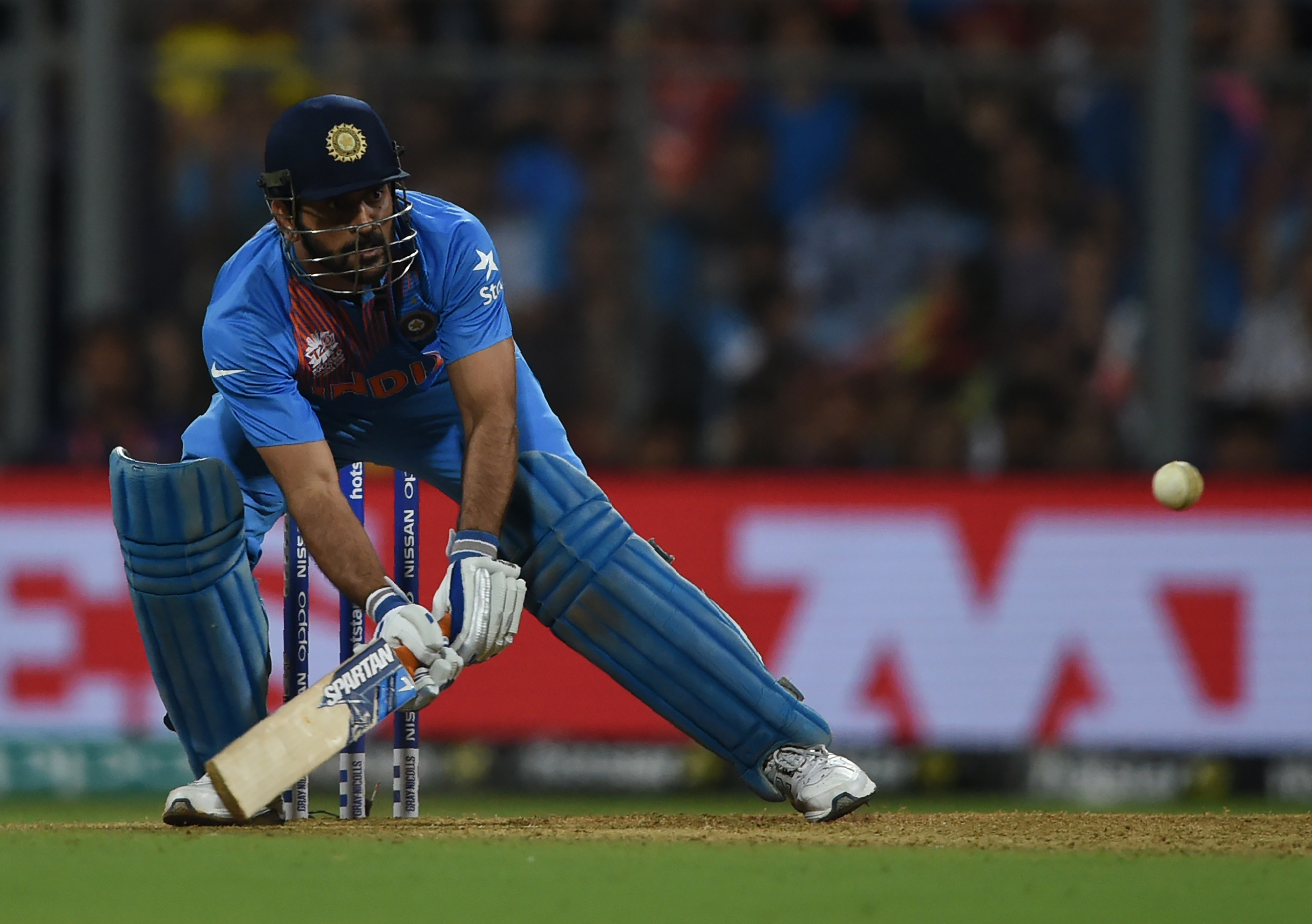 India's captain Mahendra Singh Dhoni plays a shot during the World T20 semi-final match between India and West Indies at The Wankhede Cricket Stadium in Mumbai on March 31, 2016. / AFP / INDRANIL MUKHERJEE