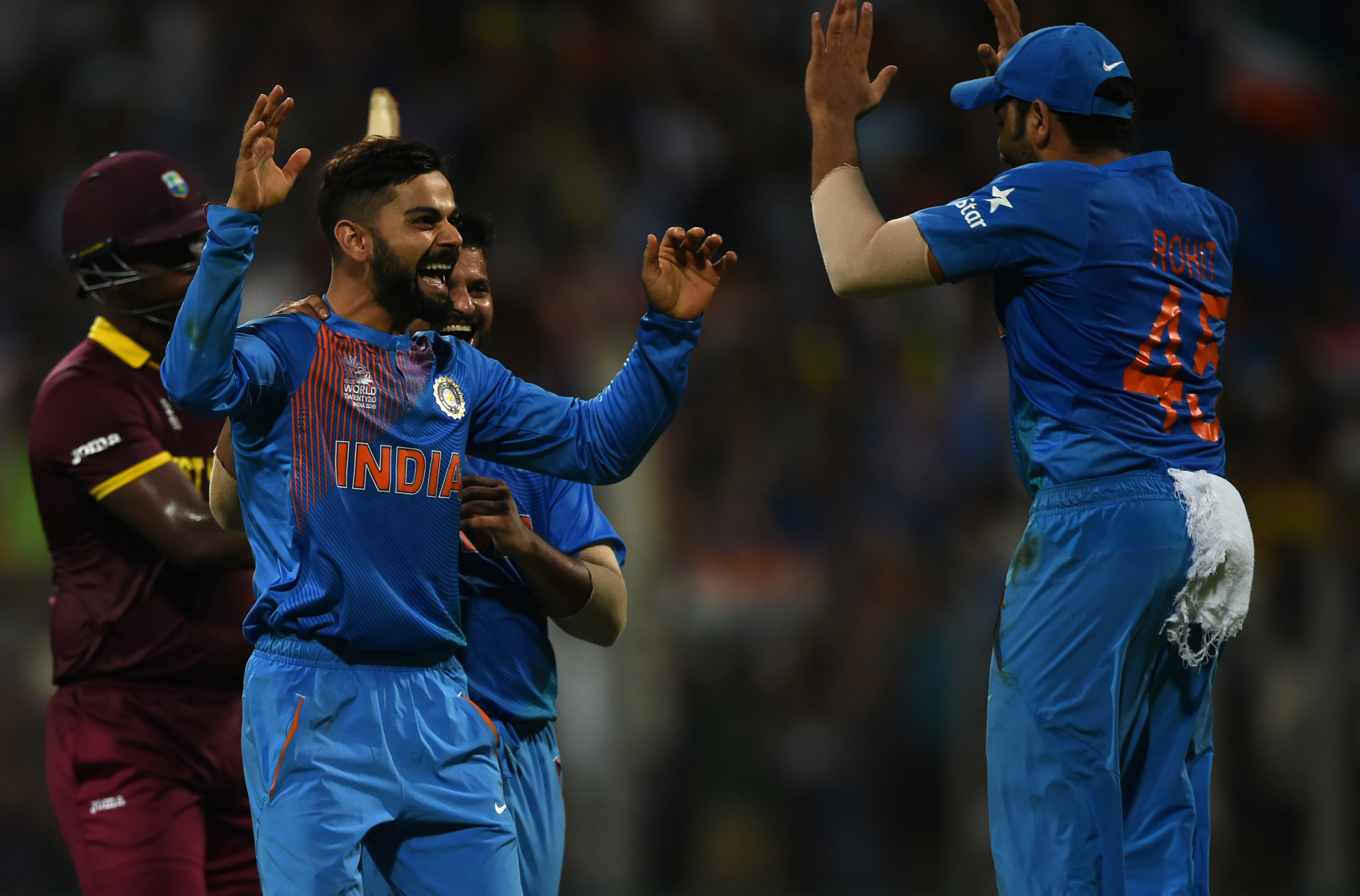 India's Virat Kohli(L)celebrates with teammate Rohit Sharma after taking the wicket of West Indies's Johnson Charles during the World T20 men's semi-final match between India and West Indies at The Wankhede Cricket Stadium in Mumbai on March 31, 2016. / AFP / INDRANIL MUKHERJEE