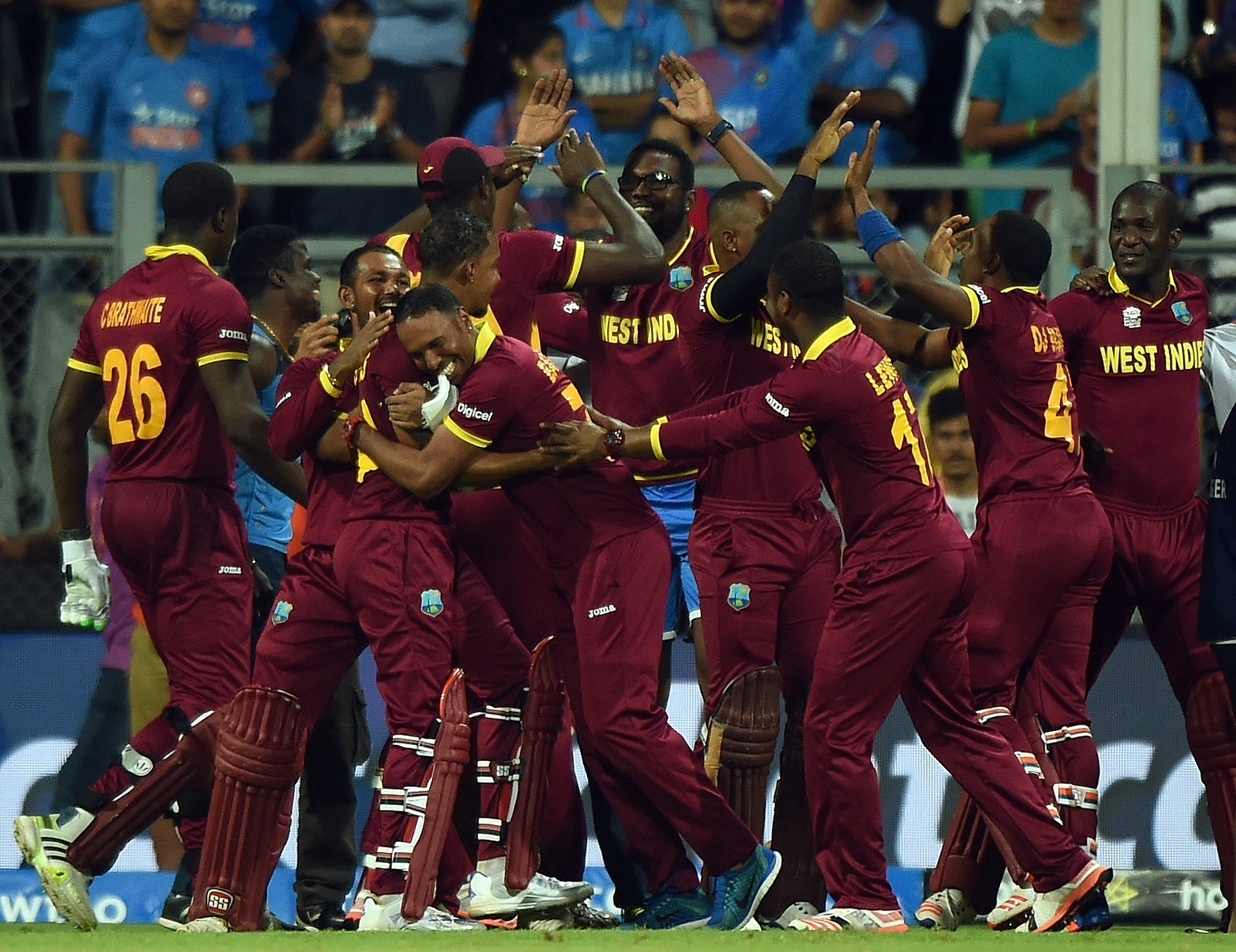 West Indies players celebrate after winning the World T20 cricket tournament semi-final match against India at The Wankhede Cricket Stadium in Mumbai on March 31, 2016. / AFP / PUNIT PARANJPE