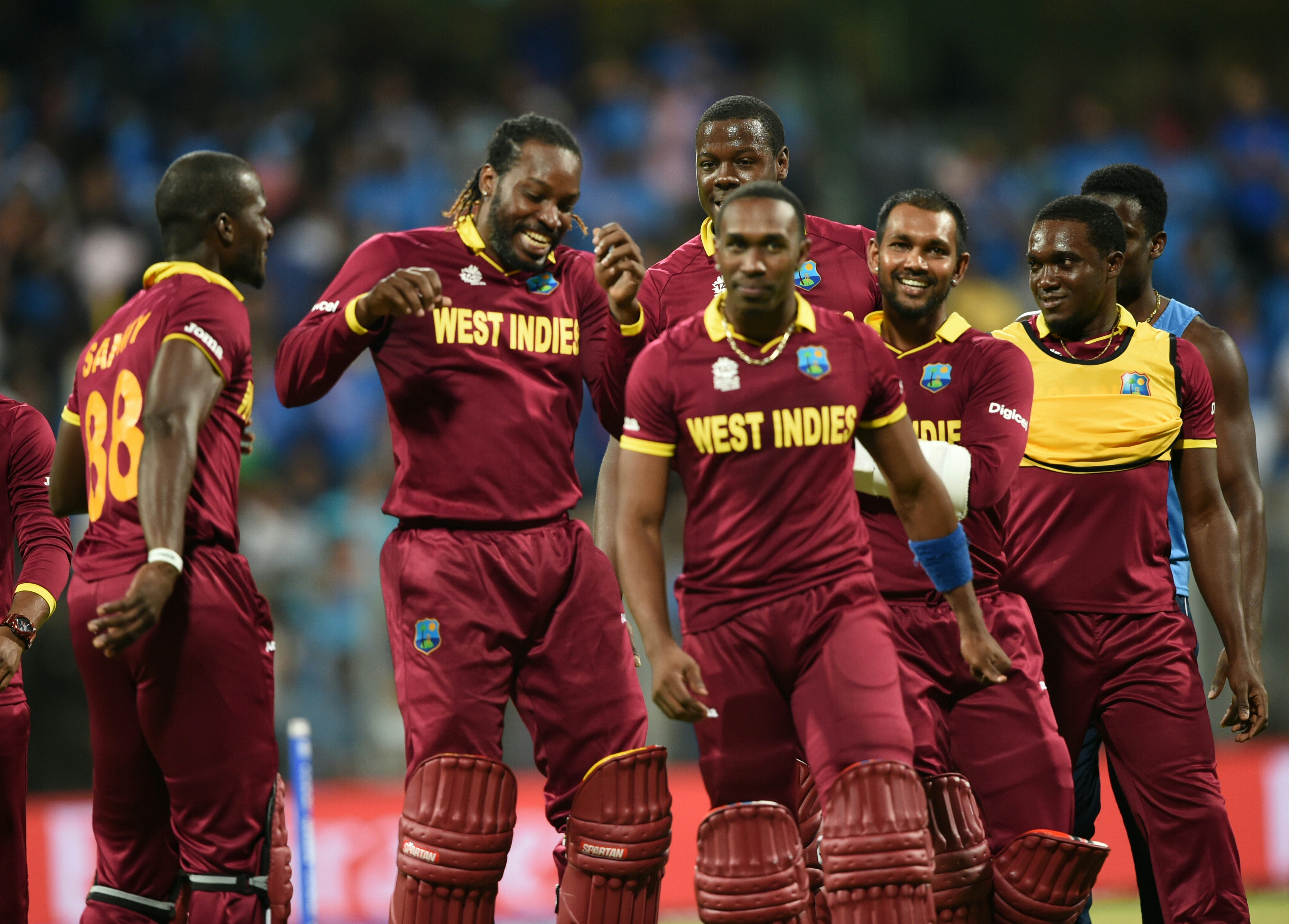 West Indies's captain Darren Sammy(L), Dwayne Bravo(C)and Chris Gayle(2L) lead teammates as they celebrate after victory in the World T20 cricket tournament second semi-final match between India and West Indies at The Wankhede Stadium in Mumbai on March 31, 2016. / AFP / INDRANIL MUKHERJEE