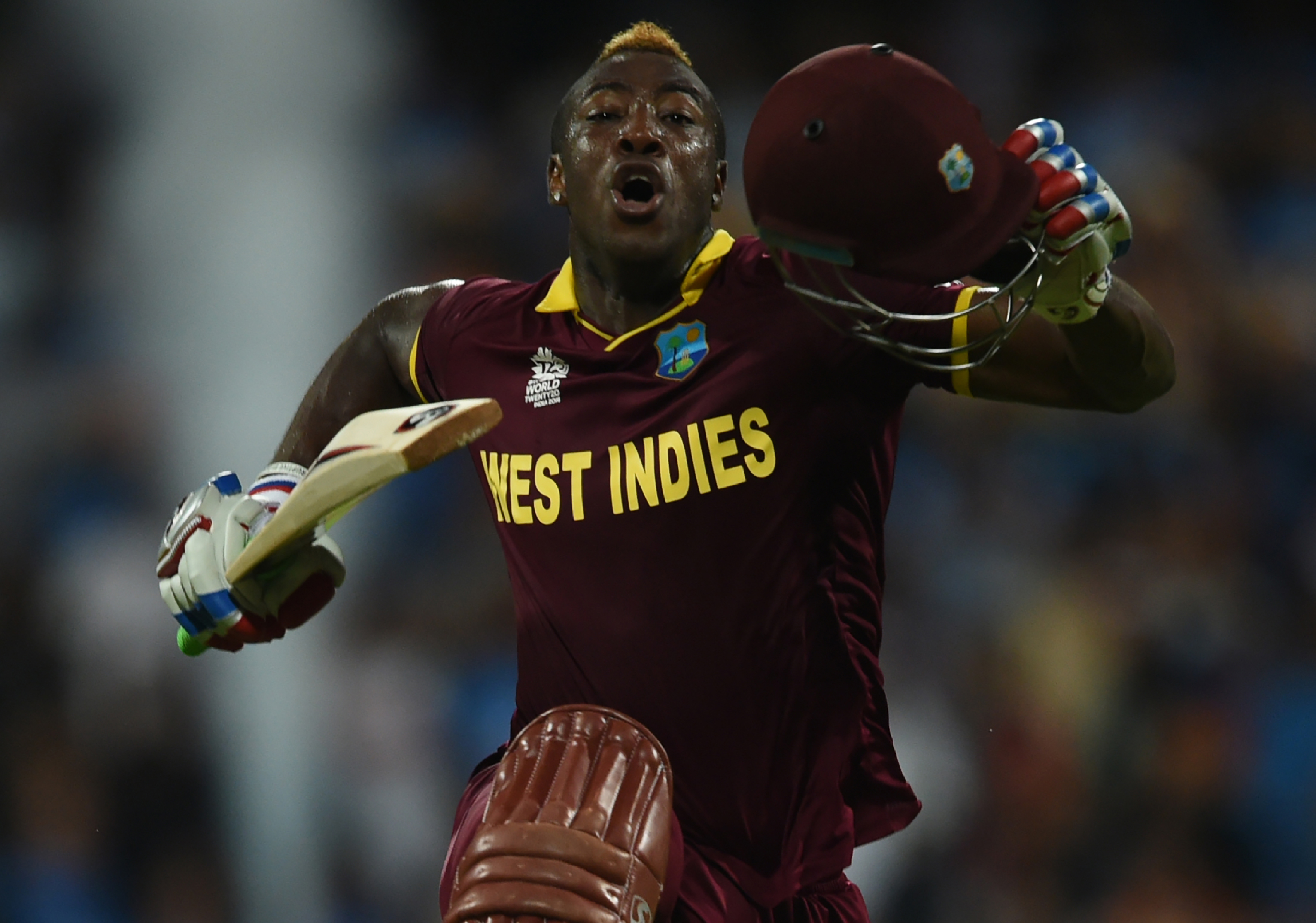 West Indies's Andre Russell celebrates after scoring the winning runs during the World T20 men's semi-final match between India and West Indies at the Wankhede stadium in Mumbai on March 31, 2016. / AFP / INDRANIL MUKHERJEE