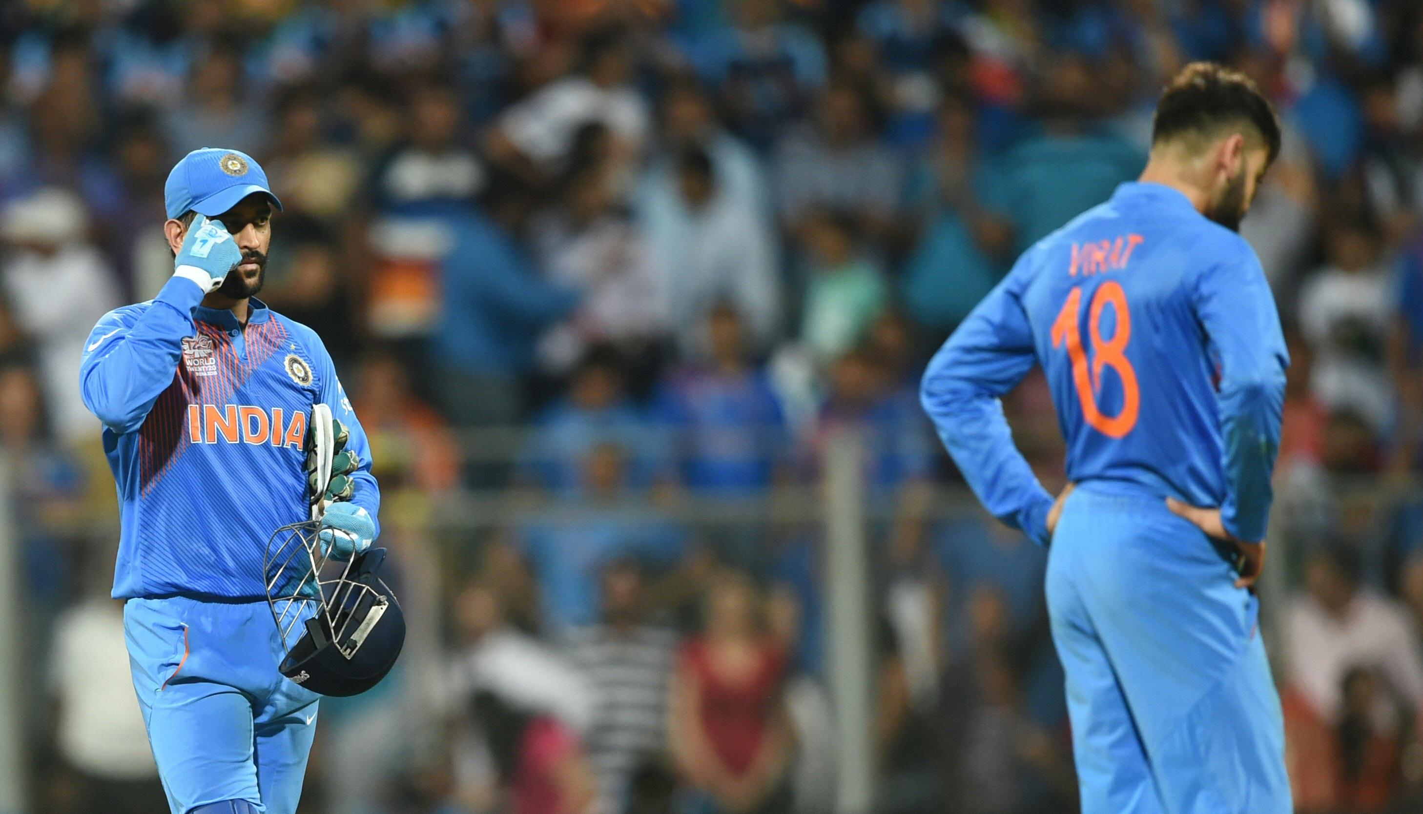 India's captain Mahendra Singh Dhoni(L) and teammate Virat Kohli react after defeat in the World T20 men's semi-final match between India and West Indies at the Wankhede stadium in Mumbai on March 31, 2016. / AFP / INDRANIL MUKHERJEE