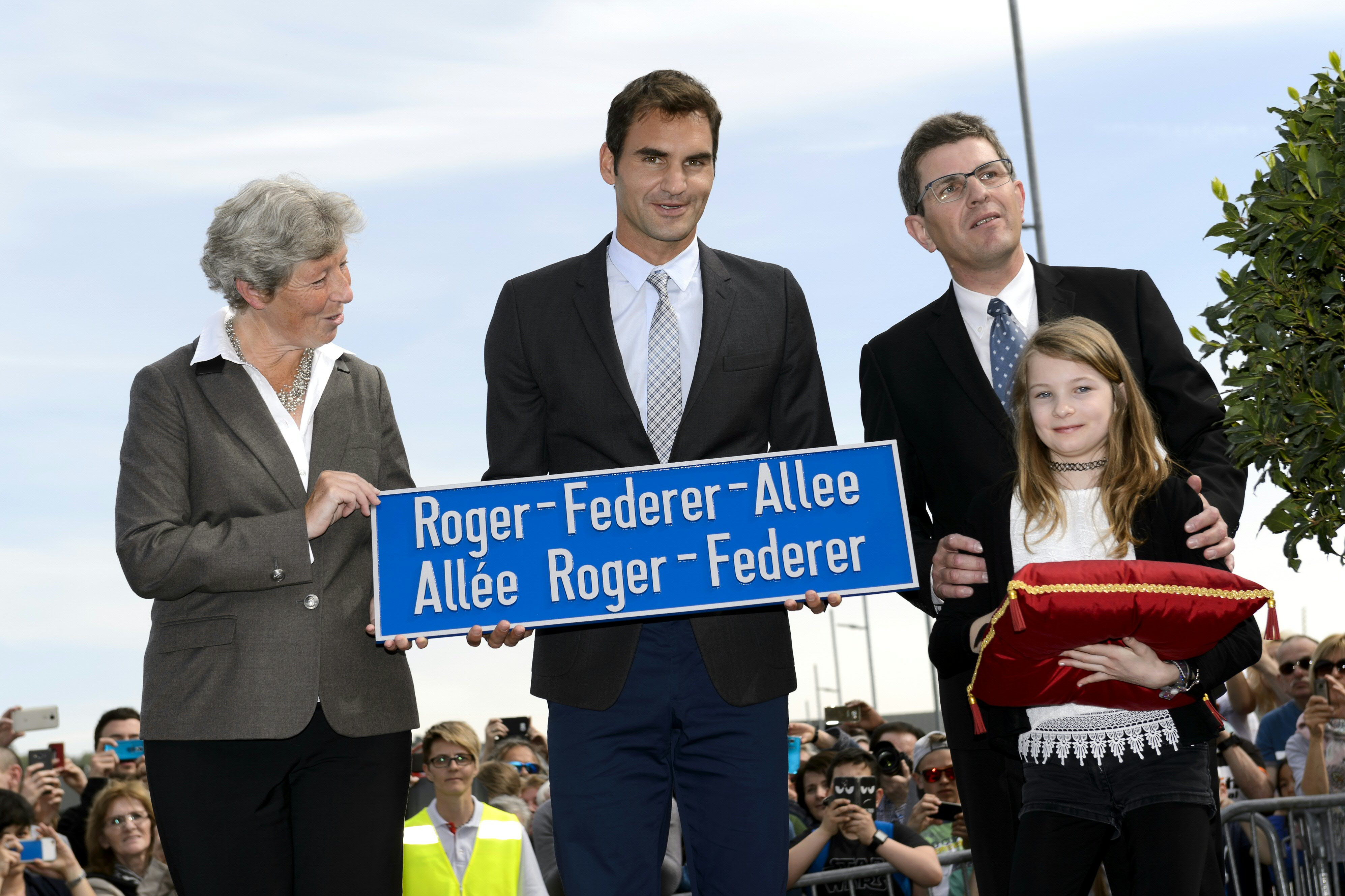 Swiss tennis champion Roger Federer (C) takes part in the ceremony marking the inauguration of a street bearing his name next to Mayor of the city of Biel, Erich Fehr (R) and member of the council of Biel Barbara Schwickert on April 21, 2016 in Biel. The street is located next to the Swiss tennis center where Federer completed its tennis studies. / AFP PHOTO / FABRICE COFFRINI