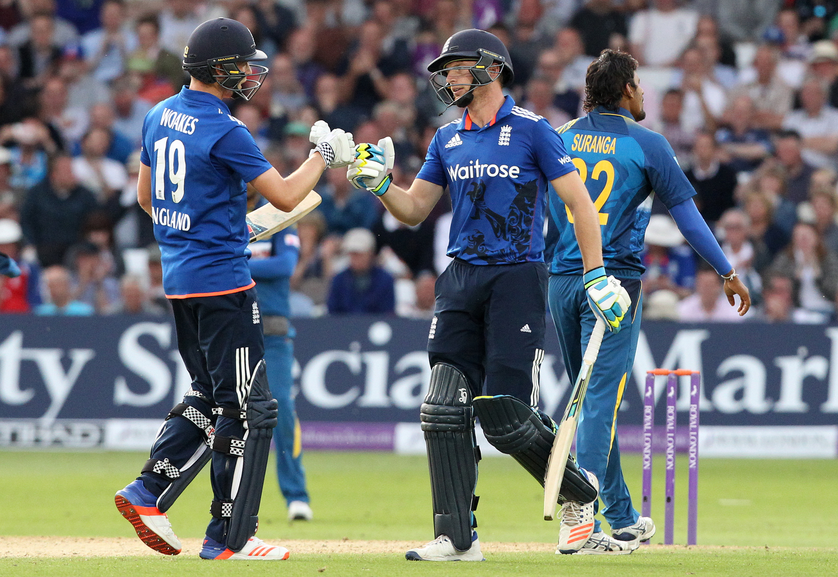 England batsman Jos Buttler gestures to England's Chris Woakes (L) during play in the first one day international (ODI) cricket match between England and Sri Lanka at Trent Bridge cricket ground in Nottingham, central England, on June 21, 2016. Sri Lanka captain Angelo Mathews top-scored with 73 as his side were held to 286 for nine by England in the first one-day international in Nottingham on Tuesday. / AFP PHOTO / Lindsey PARNABY