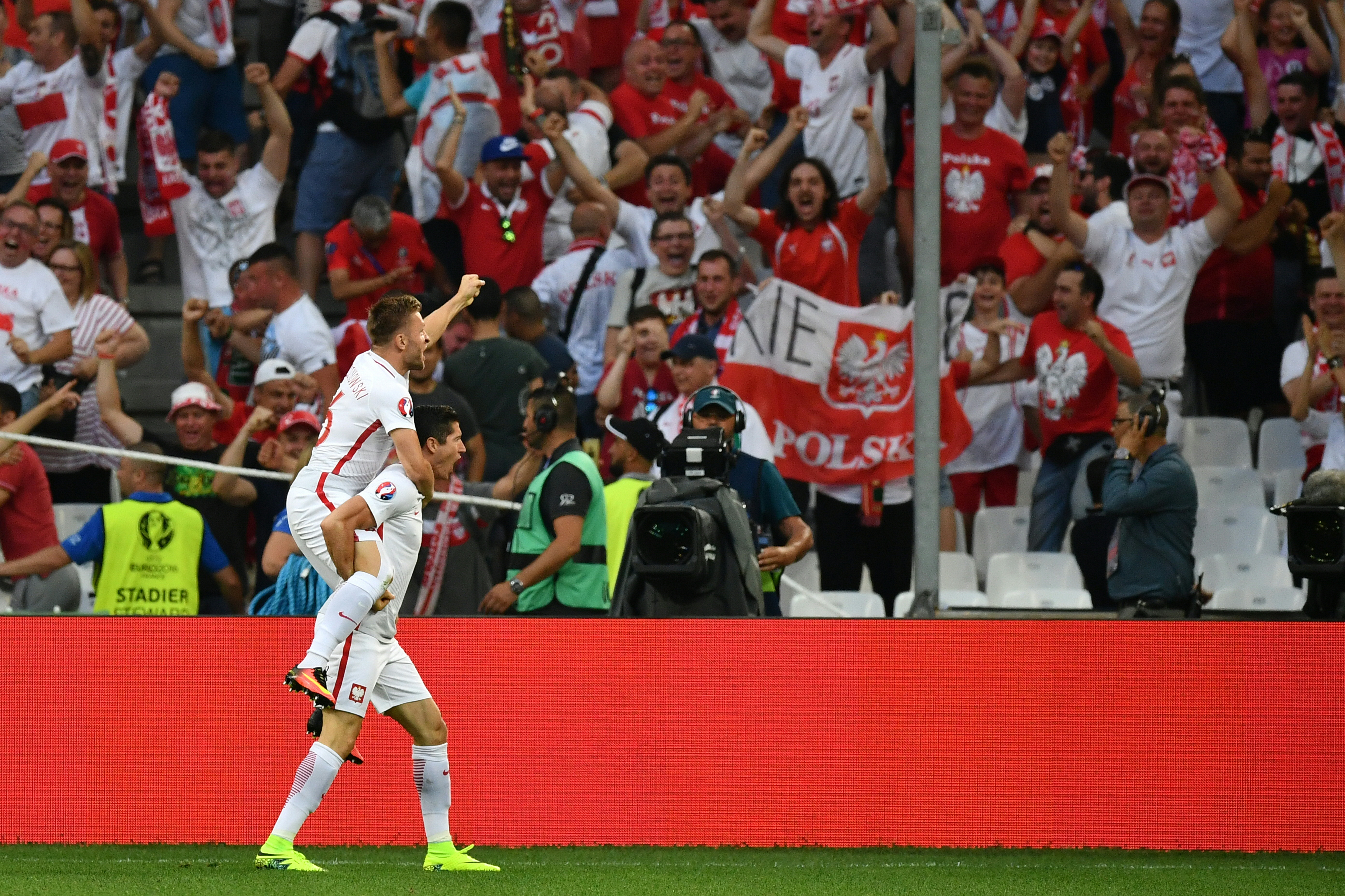 Poland's forward Robert Lewandowski (R) celebrates with Poland's midfielder Jakub Blaszczykowski (L) after scoring the first goal during the Euro 2016 quarter-final football match between Poland and Portugal at the Stade Velodrome in Marseille on June 30, 2016. / AFP PHOTO / BERTRAND LANGLOIS