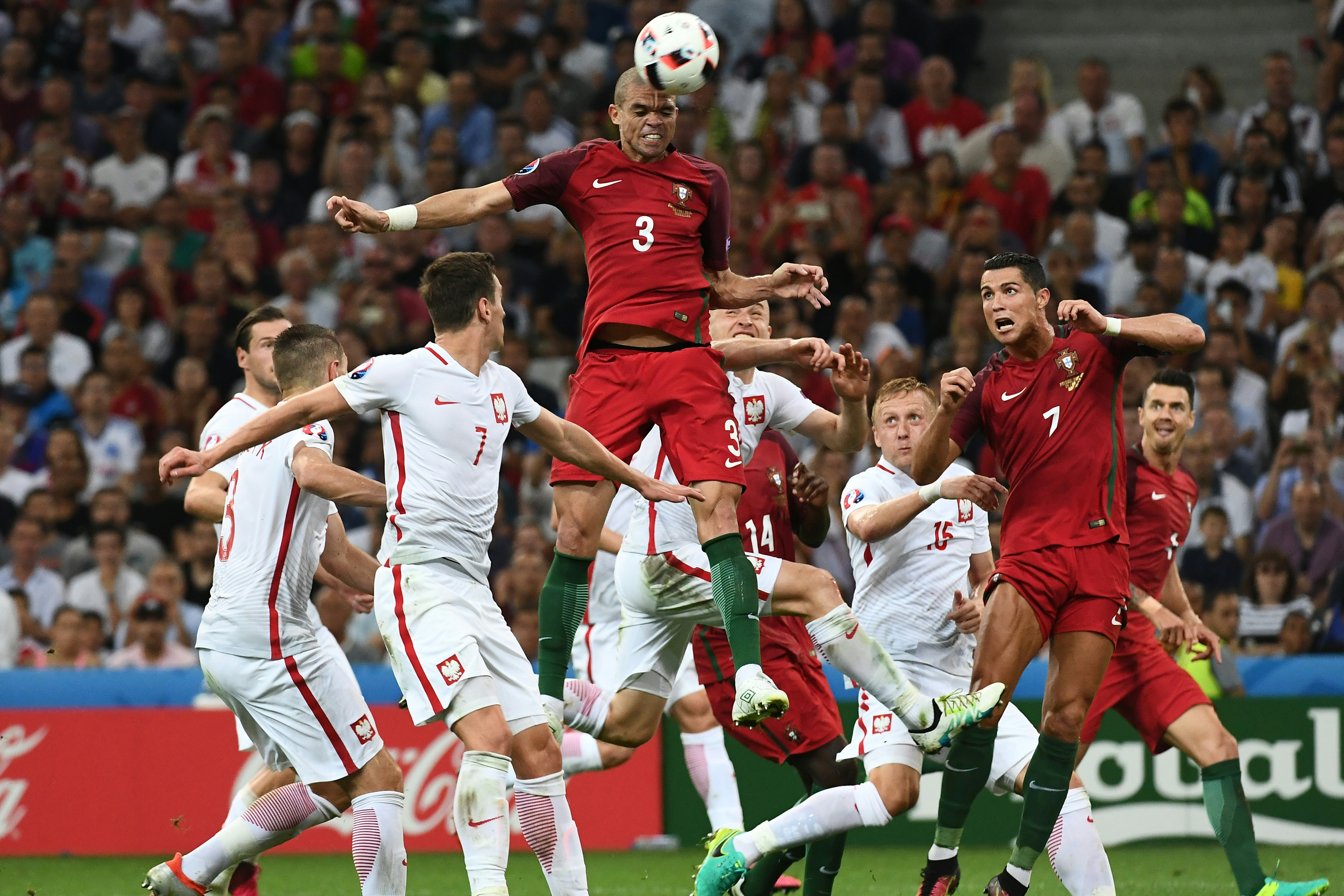 Portugal's defender Pepe (C) jumps for the ball next to Poland's forward Arkadiusz Milik (L) during the Euro 2016 quarter-final football match between Poland and Portugal at the Stade Velodrome in Marseille on June 30, 2016. / AFP PHOTO / ANNE-CHRISTINE POUJOULAT