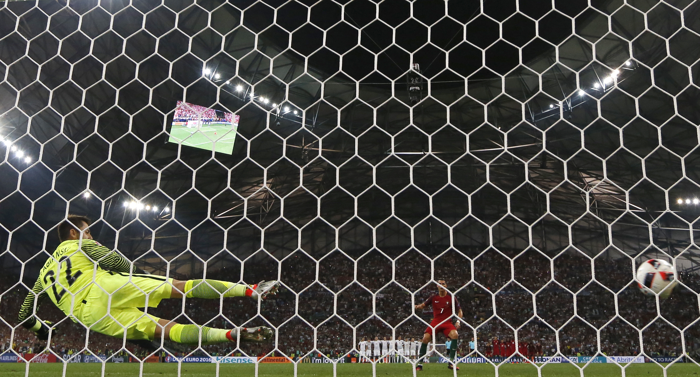 Portugal's forward Cristiano Ronaldo (R) scores the first in a penalty shoot-out during the Euro 2016 quarter-final football match between Poland and Portugal at the Stade Velodrome in Marseille on June 30, 2016. / AFP PHOTO / Valery HACHE