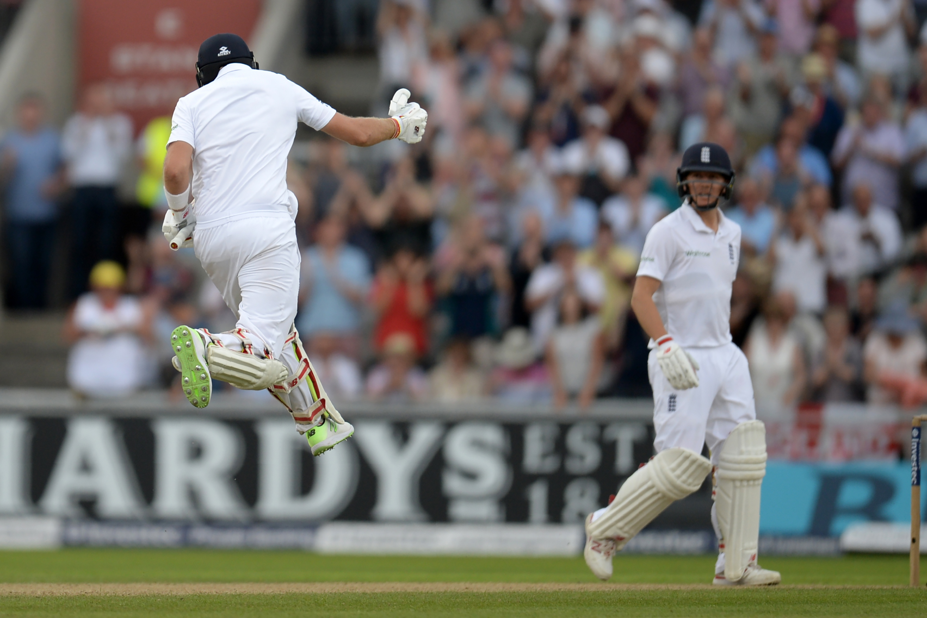 England's Joe Root (L) celebrates as he reaches his century on the first day of the second Test cricket match between England and Pakistan at Old Trafford Cricket Ground in Manchester, north west England on July 22, 2016. / AFP PHOTO / OLI SCARFF