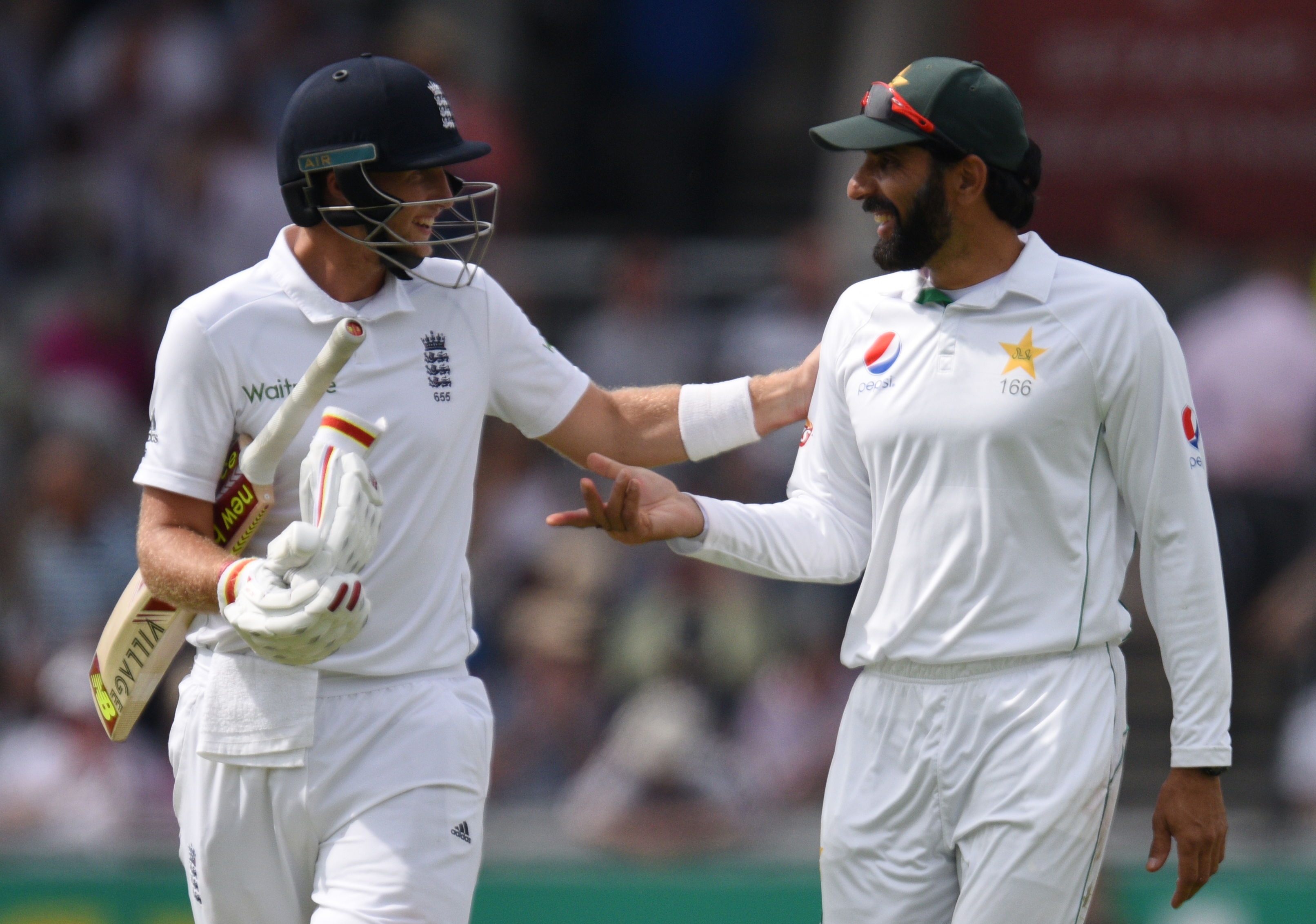 England's Joe Root chats to Pakistan's captain Misbah-ul-Haq (R) as they walk off for tea on the second day of the second Test cricket match between England and Pakistan at Old Trafford Cricket Ground in Manchester, England on July 23, 2016. / AFP PHOTO / OLI SCARFF