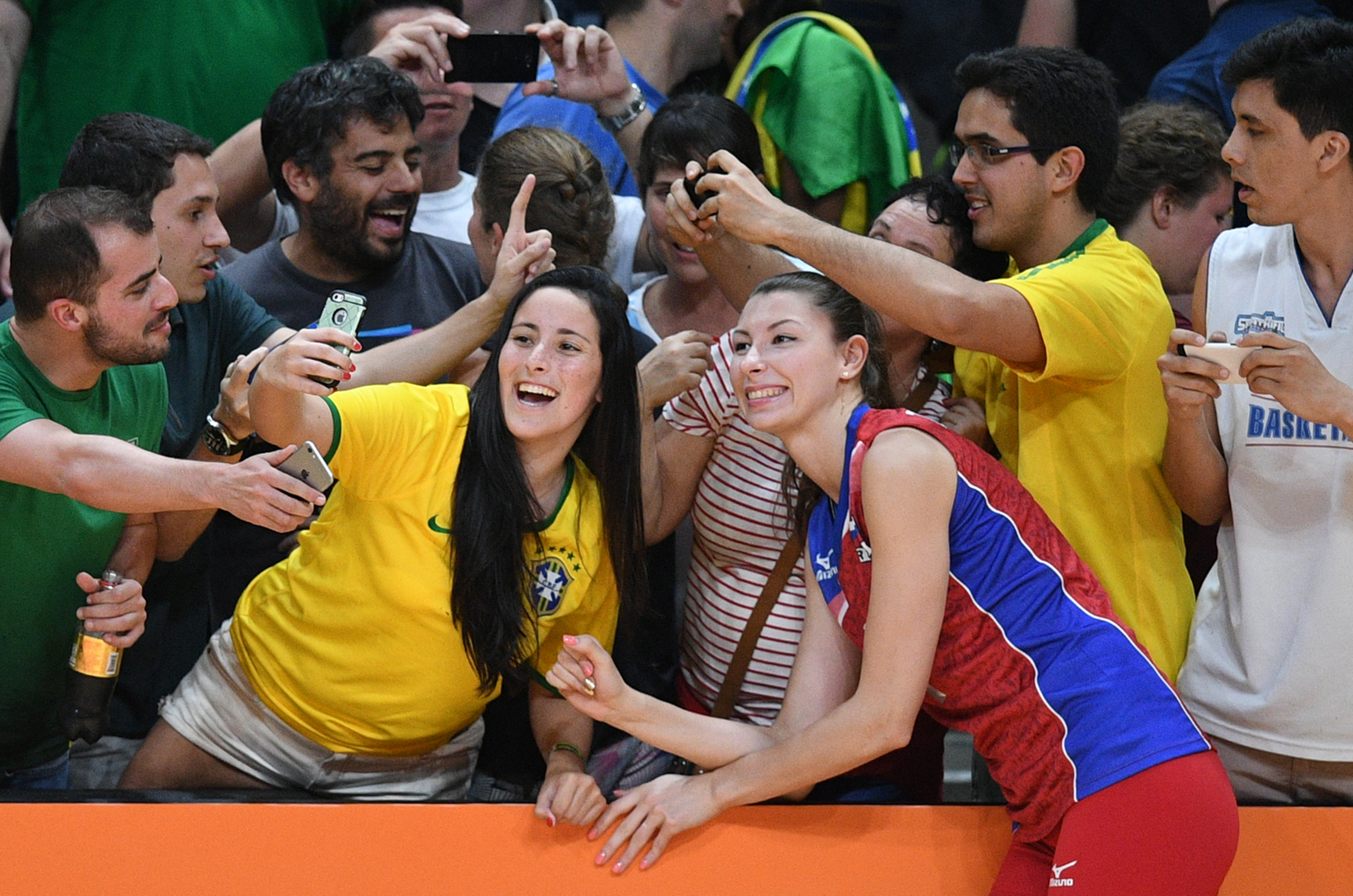 Russia's Irina Zarayazhko poses for a picture with supoprters after her team won the women's qualifying volleyball match between Russia and South Korea at the Maracanazinho stadium in Rio de Janeiro on August 8, 2016, during the 2016 Rio Olympics. / AFP PHOTO / Johannes EISELE
