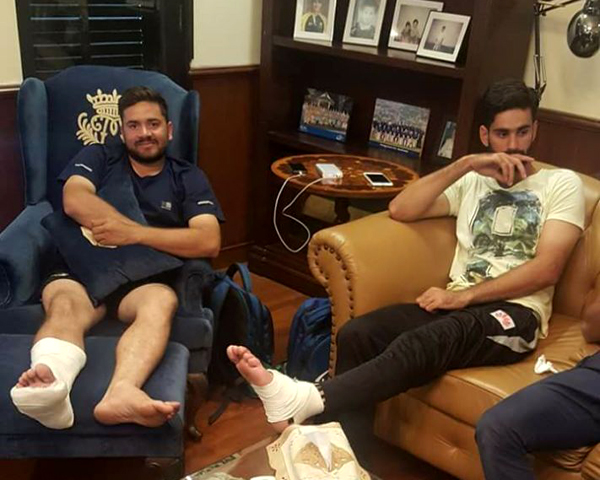 Pakistan cricketer Hammad Azam (R) sits with his first-class teammate after getting their injuries treated.