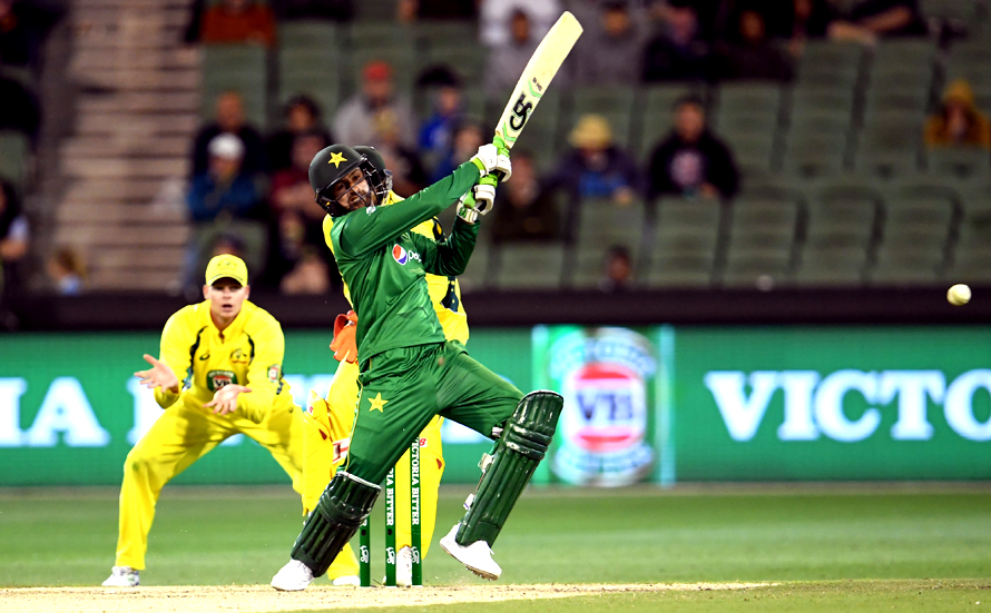 Pakistan batsman Shoaib Malik hits out at the bowling as Australia's captain Steve Smith looks on. (PHOTO: AFP)