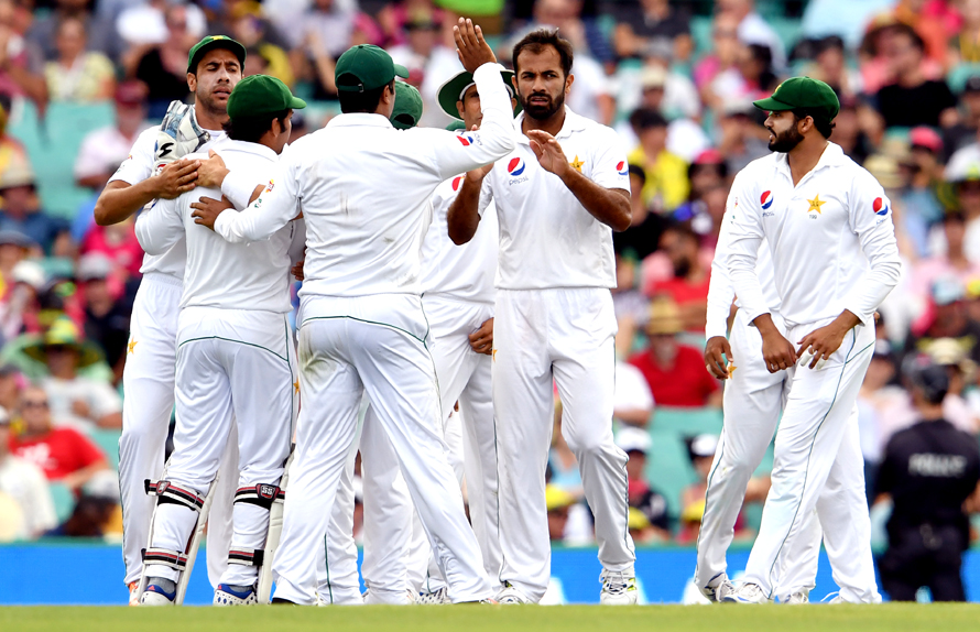 Pakistan paceman Wahab Riaz (centre R) celebrates with teammates after dismissing Australia's batsman Usman Khawaja during the first day of the third cricket Test match at the SCG in Sydney on January 3, 2017. / AFP PHOTO / WILLIAM WEST / IMAGE RESTRICTED TO EDITORIAL USE - STRICTLY NO COMMERCIAL USE