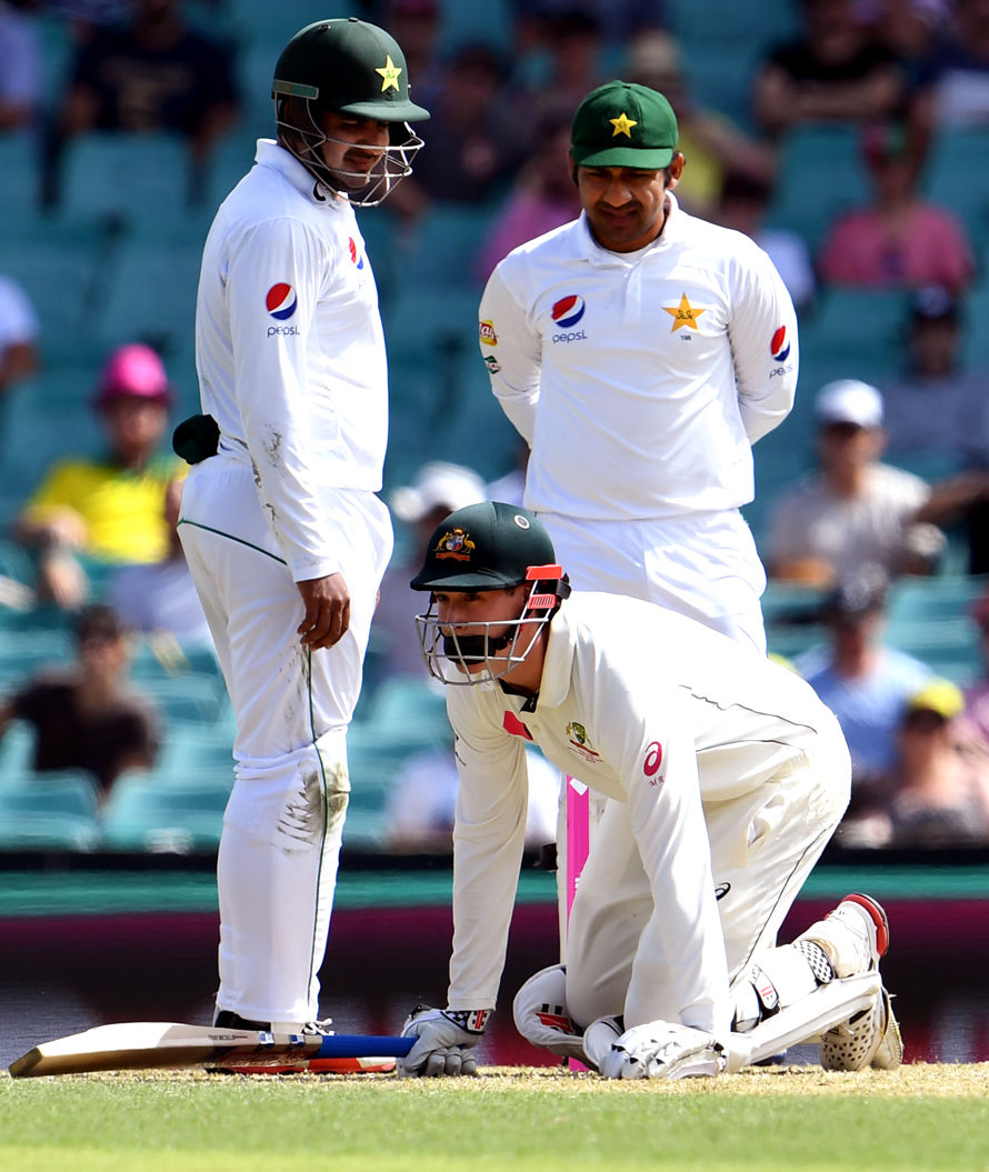 Australia's batsman Matt Renshaw (C) regains his feet after being hit on the helmet by a bouncer as Sharjeel Khan (L) and Sarfraz Ahmed (R) of Pakistan look on during the first day of the third cricket Test match at the SCG, in Sydney on January 3, 2017. / AFP PHOTO / WILLIAM WEST / IMAGE RESTRICTED TO EDITORIAL USE - STRICTLY NO COMMERCIAL USE