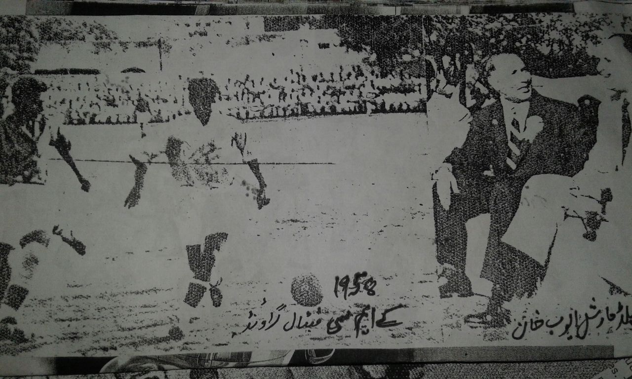 Field Marshal Ayub Khan watching a game from sideline at KMC Football Stadium.