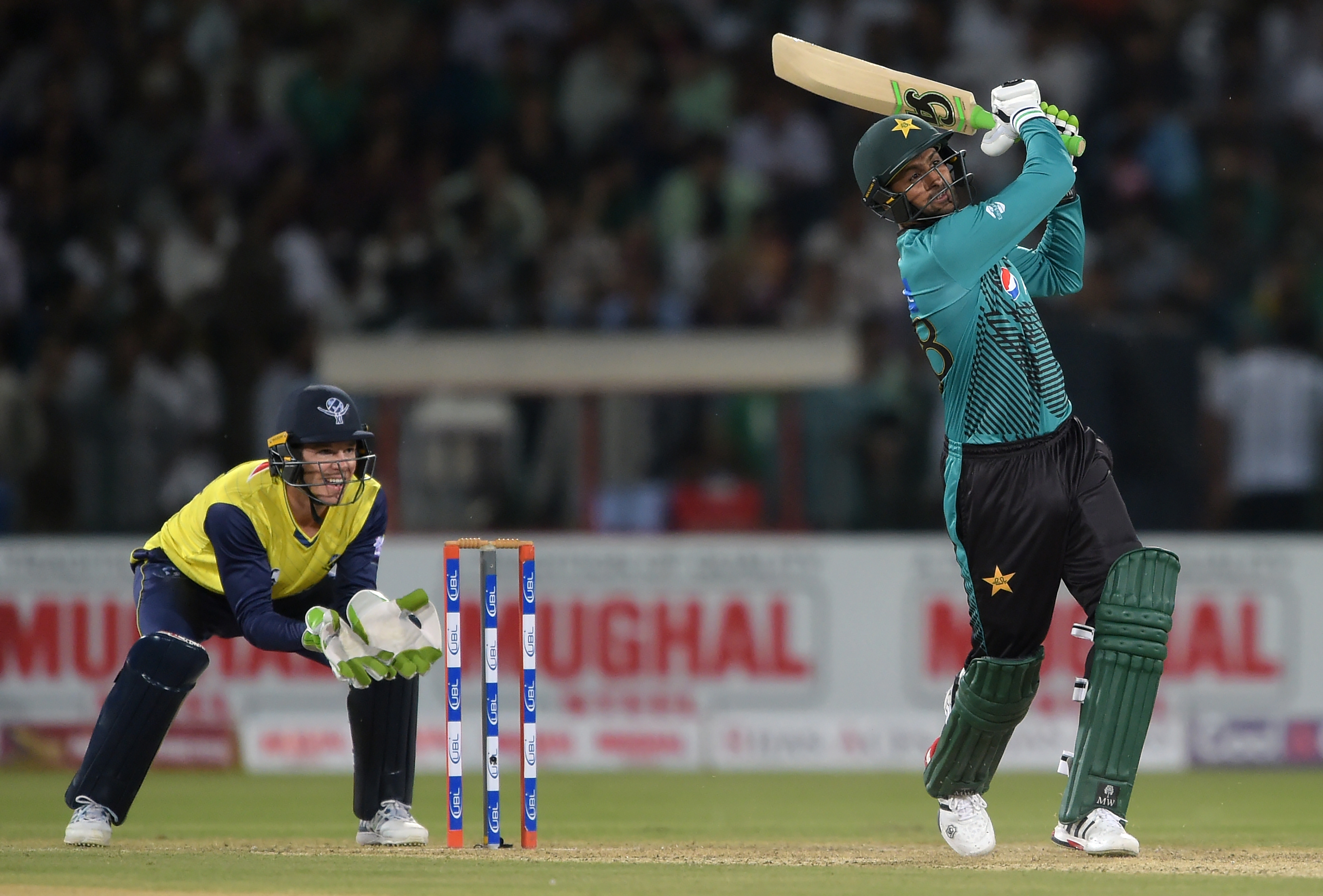 Pakistani batsman Shoaib Malik (R) hits a six as World XI wicketkeeper Tim Paine looks on during the second Twenty20 International match between the World XI and Pakistan at the Gaddafi Cricket Stadium in Lahore on September 13, 2017. / AFP PHOTO / AAMIR QURESHI